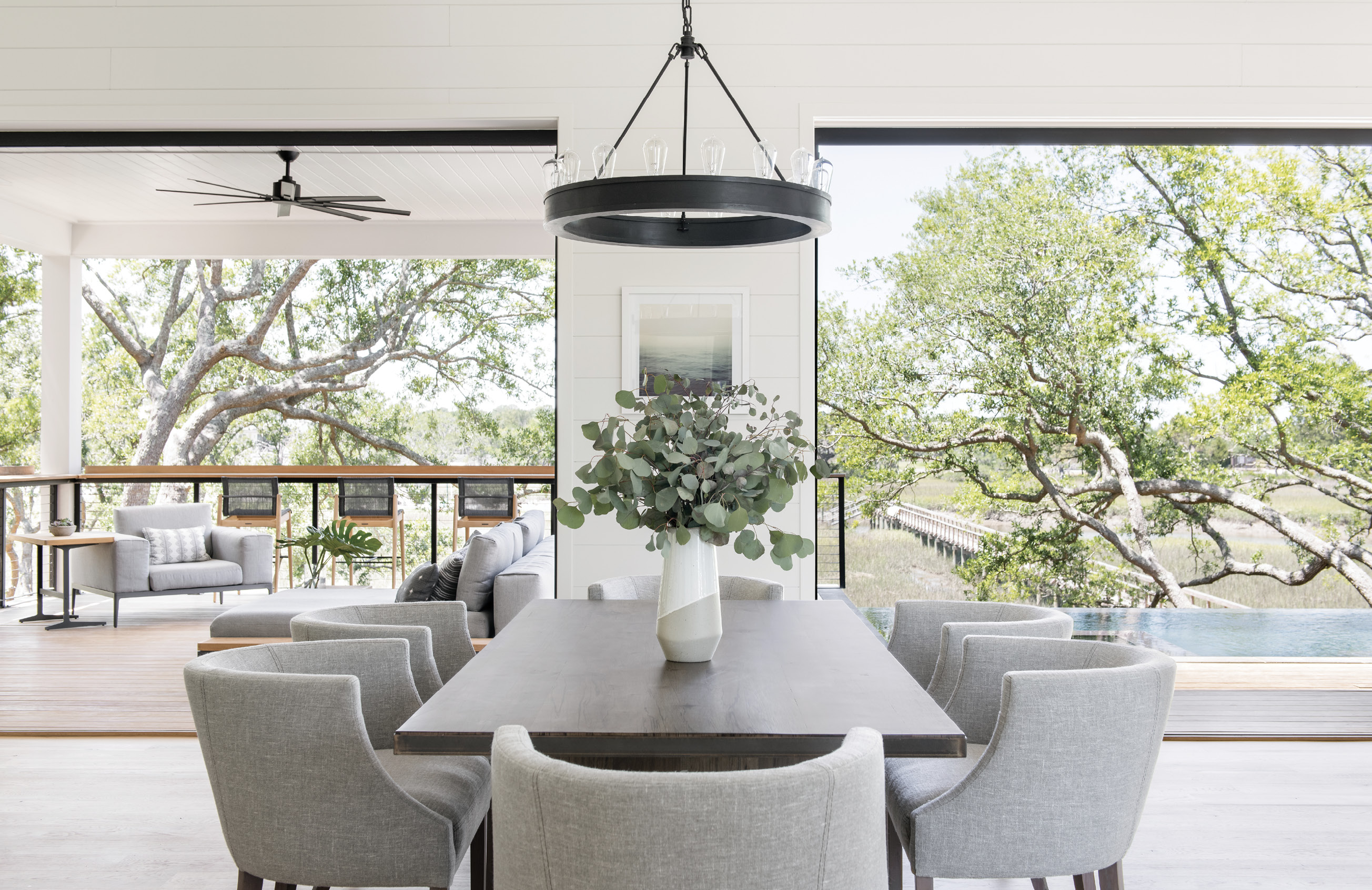 """On A Limb: """"From the start, my clear goal was to bring the outdoors in for an open-living, tree-house concept,"""" explains Melissa Lenox, who designed the interiors of the home. """"All main living spaces and the master were intended to bring the unique and beautiful Lowcountry nature indoors."""" She chose neutral colors for the furniture, such as the HomeNature sectional and Verellen dining chairs, and incorporated soft marsh hues in accent pieces like paintings, rugs, and pillows."""