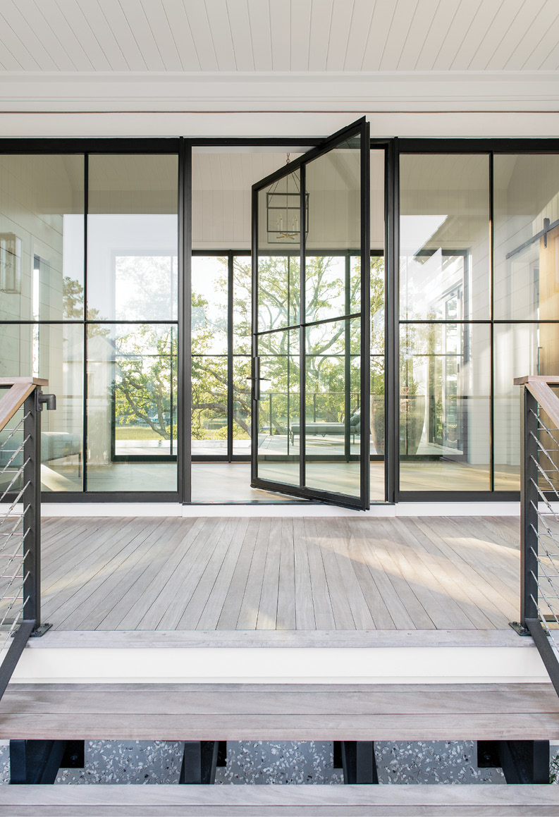 Steeling Beauty: At the top of the home's floating outdoor staircase, the custom steel and glass pivot door made by Arcadia Custom Building Materials provides entry to the glass breezeway, its industrial feel softened by a serene view of oak trees and marsh just beyond.
