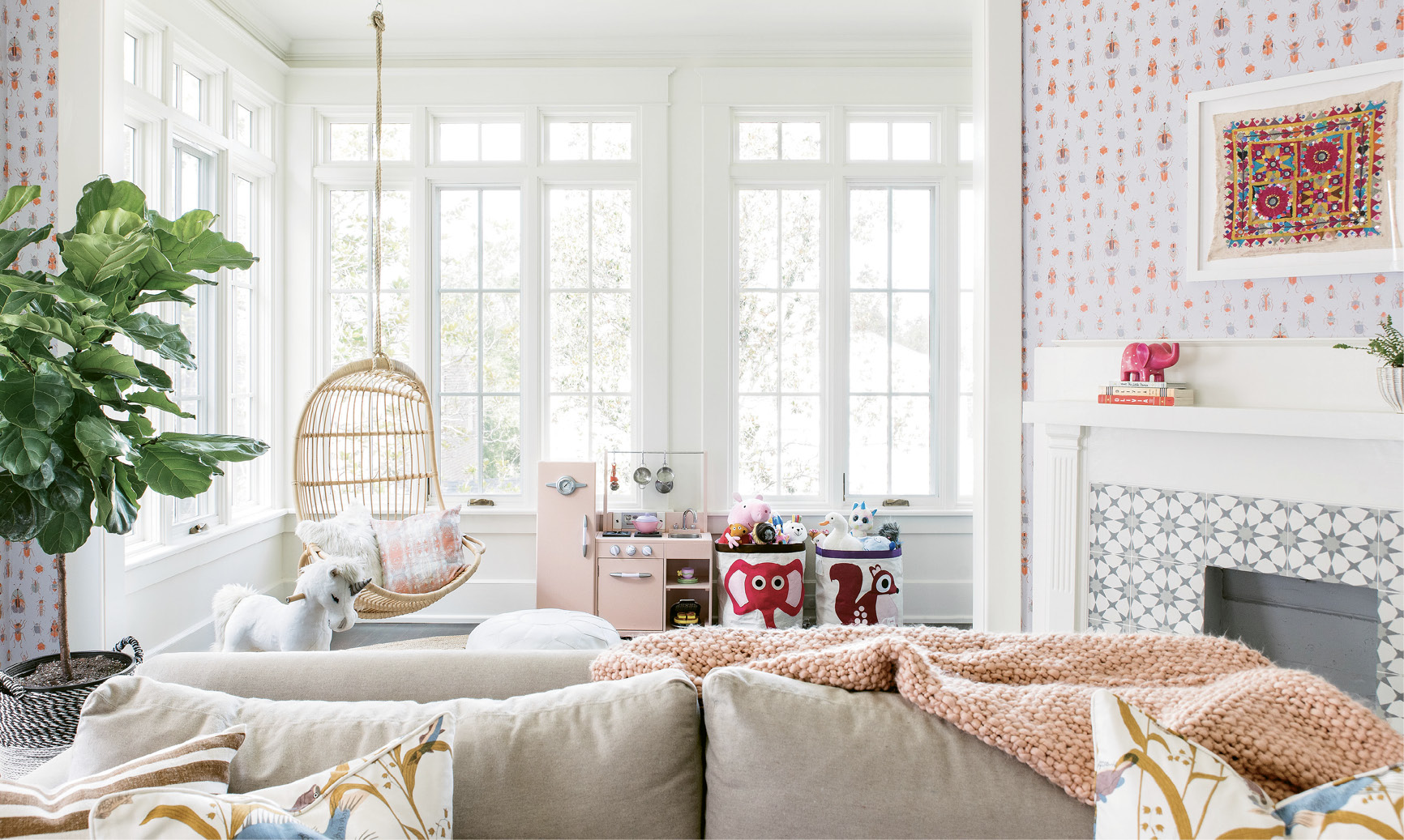 "In the vibrant playroom, comfy, kid-friendly furniture—like the Serena & Lily hanging chair and Lee Industries pullout sofa outfitted in performance fabric—mix with playful décor, including a vintage textile interior designer Melissa Lenox found in Jodhpur, India, and Lulie Wallace's ""Meyers"" wallpaper."