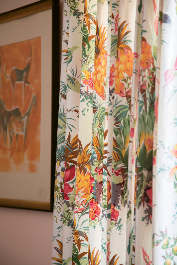 Floral drapes in punchy hues of orange, pink, and green add a beachy aesthetic to the home office.