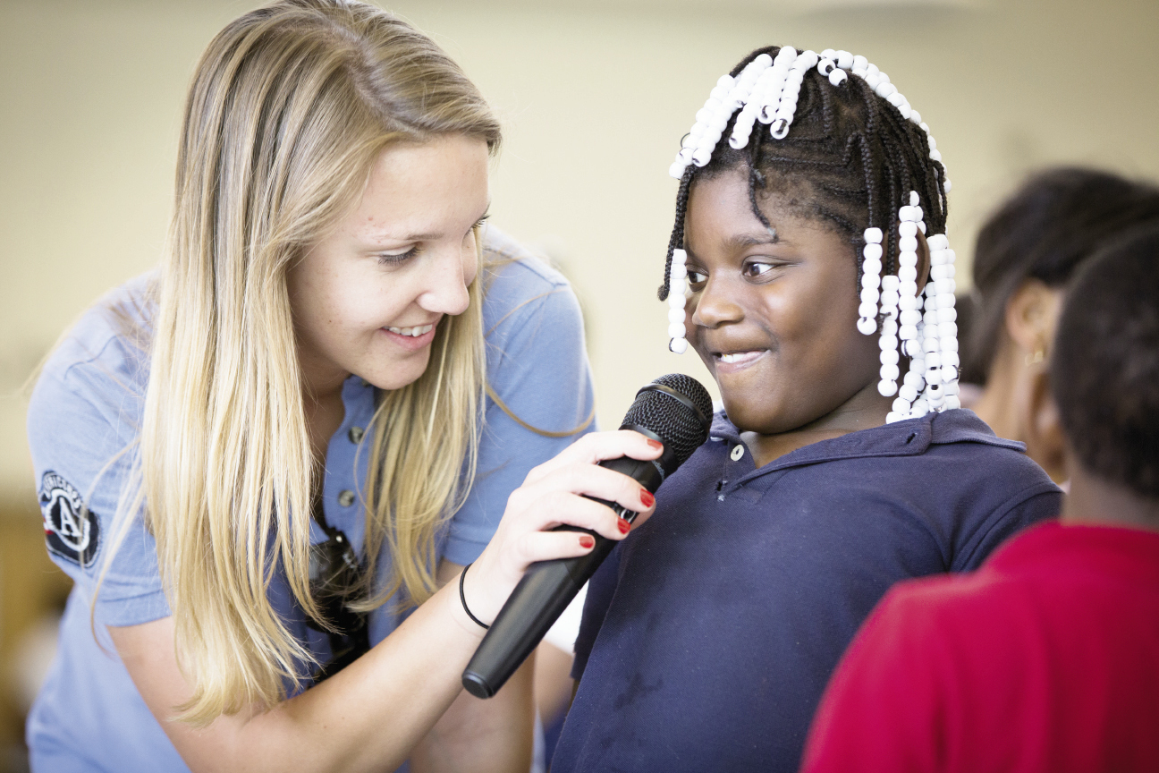 Program assistant Katie Barton  encourages Xavi'Onna Harley on the microphone.