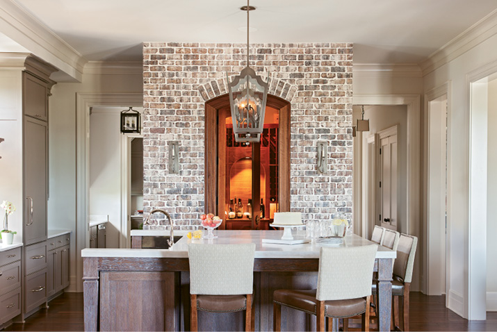 in the mix: Accent walls of brick and butted board help to set a welcoming, laid-back tone, while gilt-framed artwork and fixtures from Circa and Urban Electric add touches of elegance.