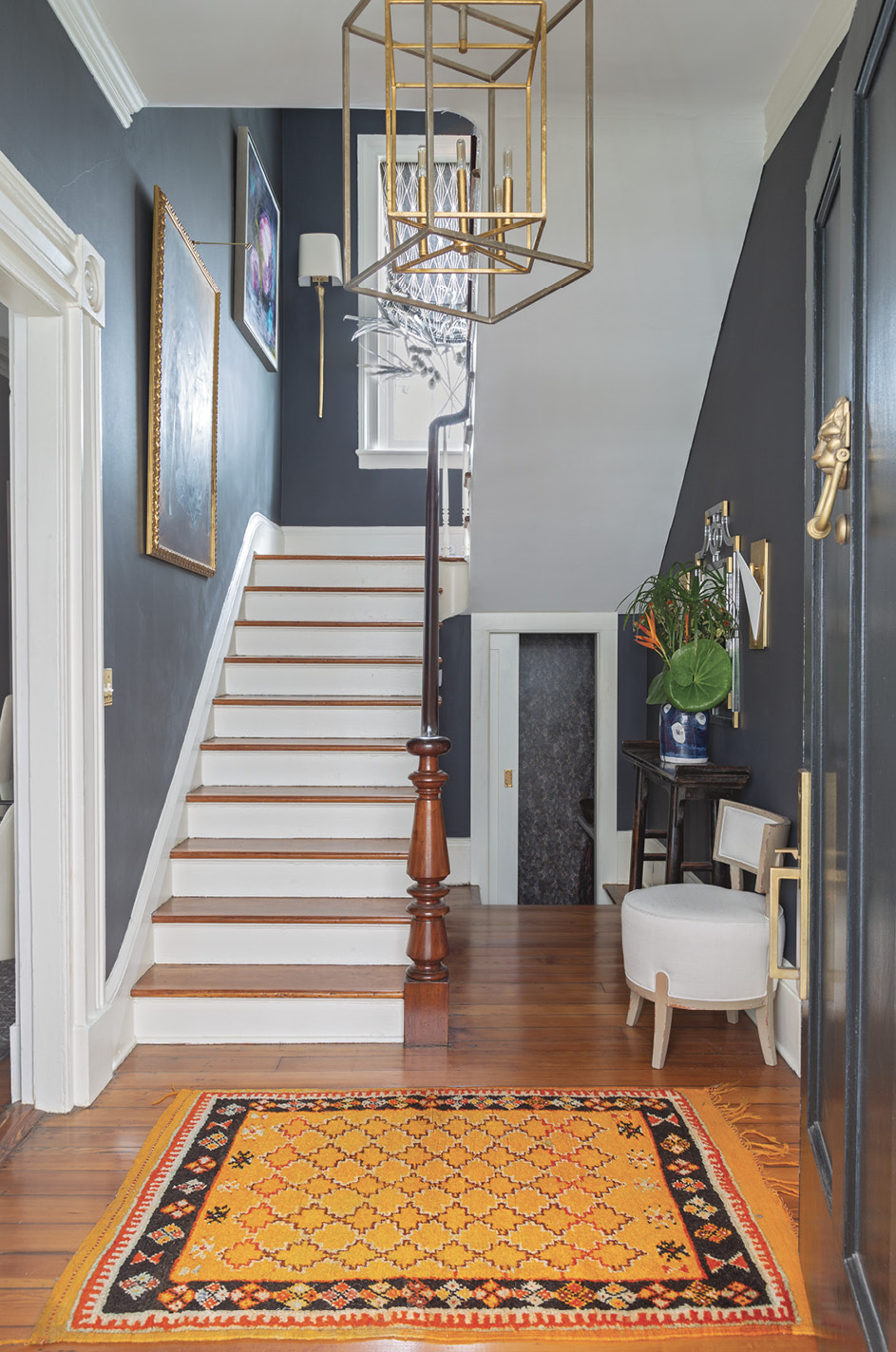 "High Contrast: The entry and stairwell are painted in Benjamin Moore's striking ""Wrought Iron."" Offset by white trim and the wooden treads and handrail, the color adds personality to a utilitarian space and helps the gold accents (wall sconces and chandeliers from Circa Lighting) pop."