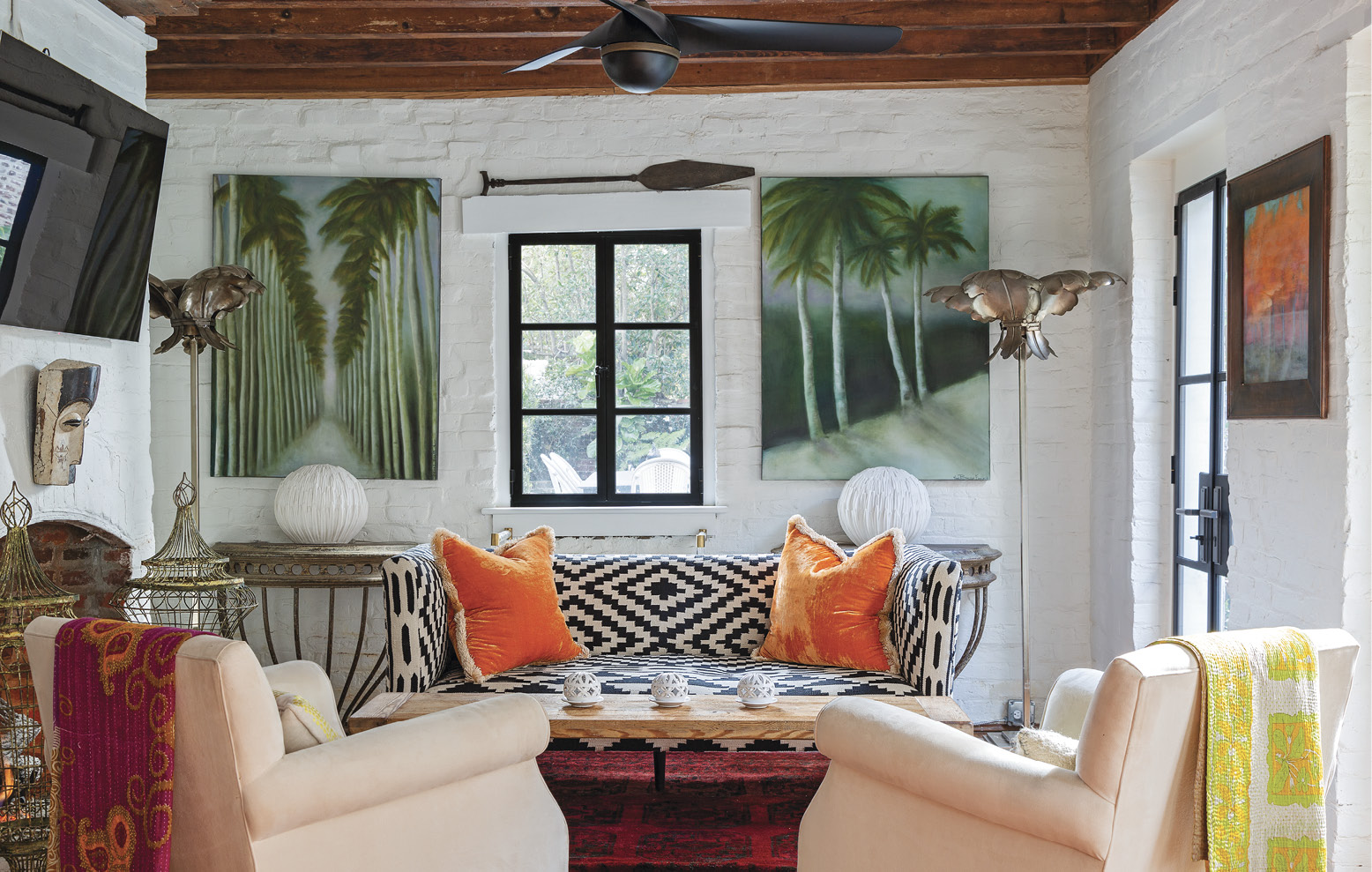 The former kitchen house is now a charming guest suite—and Betsy's favorite space to watch the morning news. A kilim-upholstered sofa with orange velvet pillows from Fritz Porter lends a Middle Eastern vibe to the cozy cottage, while palm trees painted by Betsy mimic the vintage floor lamps.