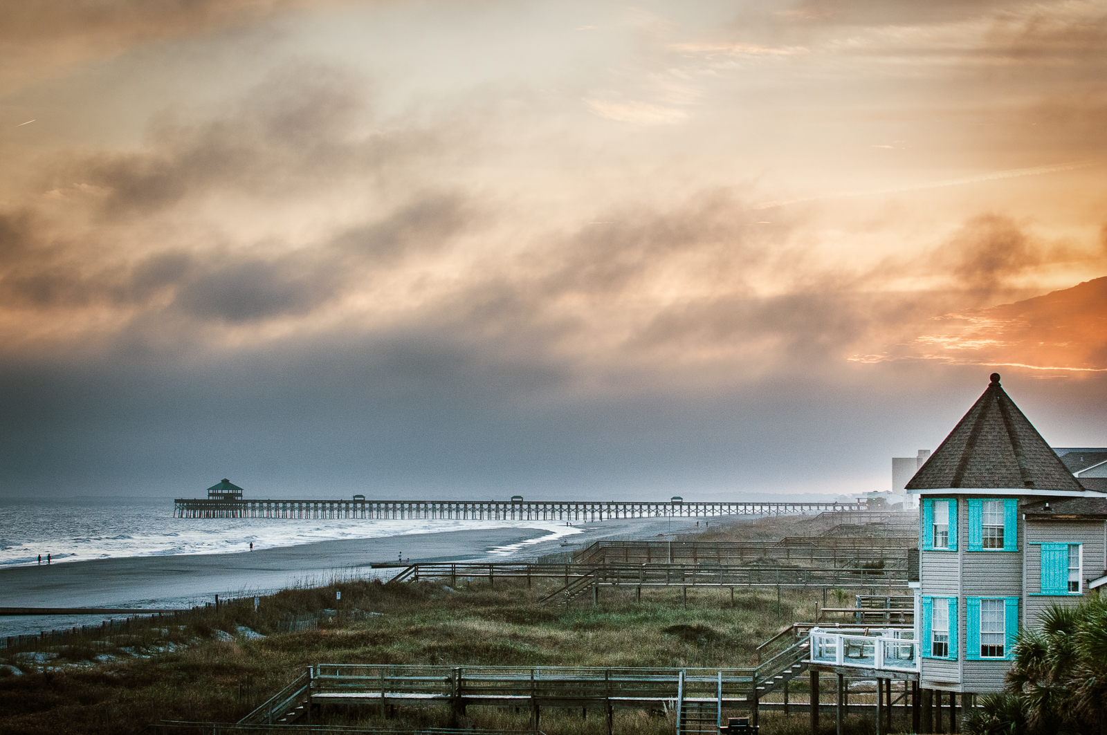 "HONORABLE MENTION Professional category: Folly Fog by Pamela Oliveras ""I drove down to Folly in January to capture the sunset and right as I got there a fog started rolling in. But it made the shot for me with the bit of the sunset orange pushing through and the blue of the beach house—gorgeous!"""