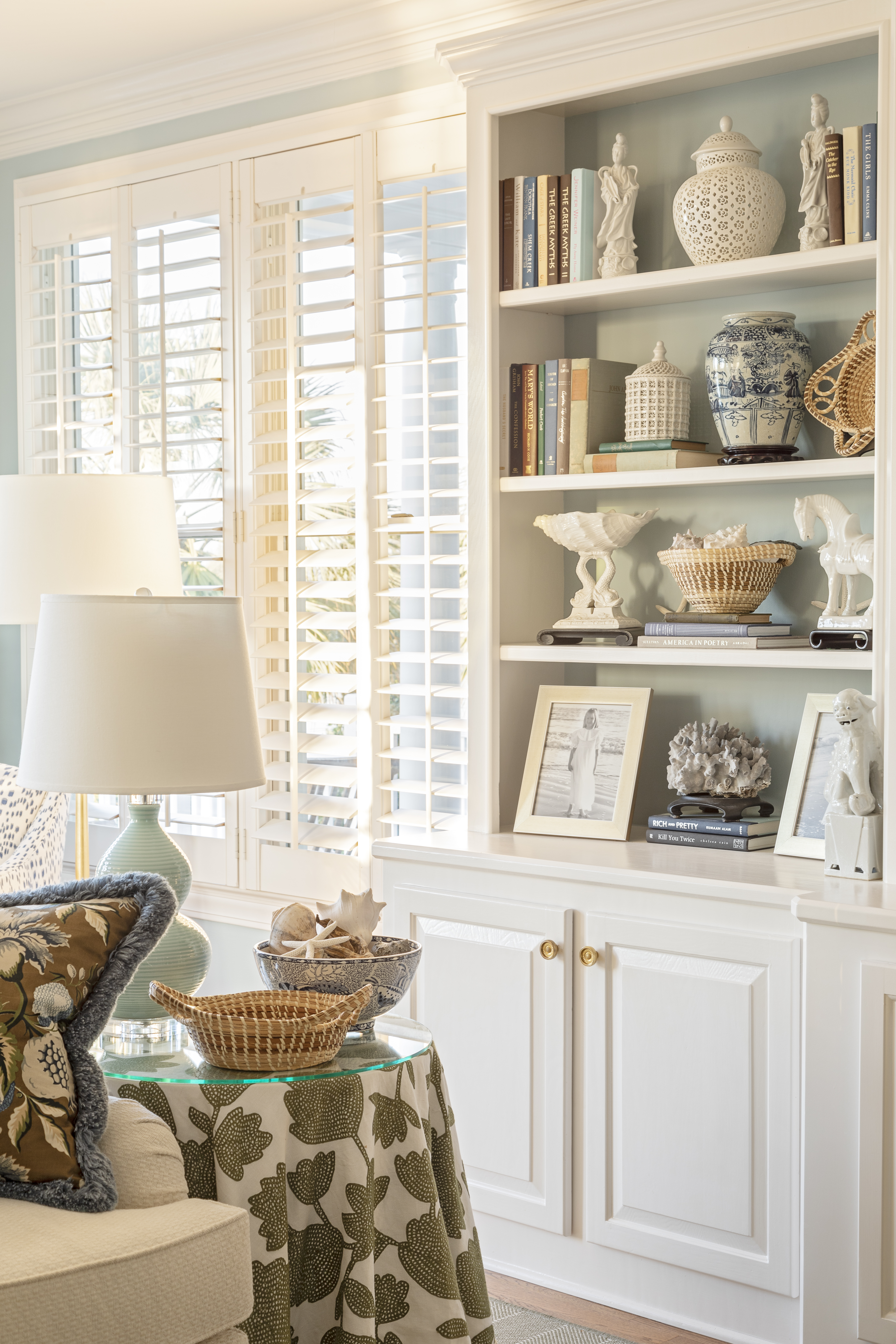 Family mementoes, from treasured photos to an expansive collection of sweetgrass baskets, take pride of place in the built-in shelving, which Horton augmented with aged brass reproduction shutter knobs from the Nathaniel Russel House, sourced at Charleston Hardware Co.