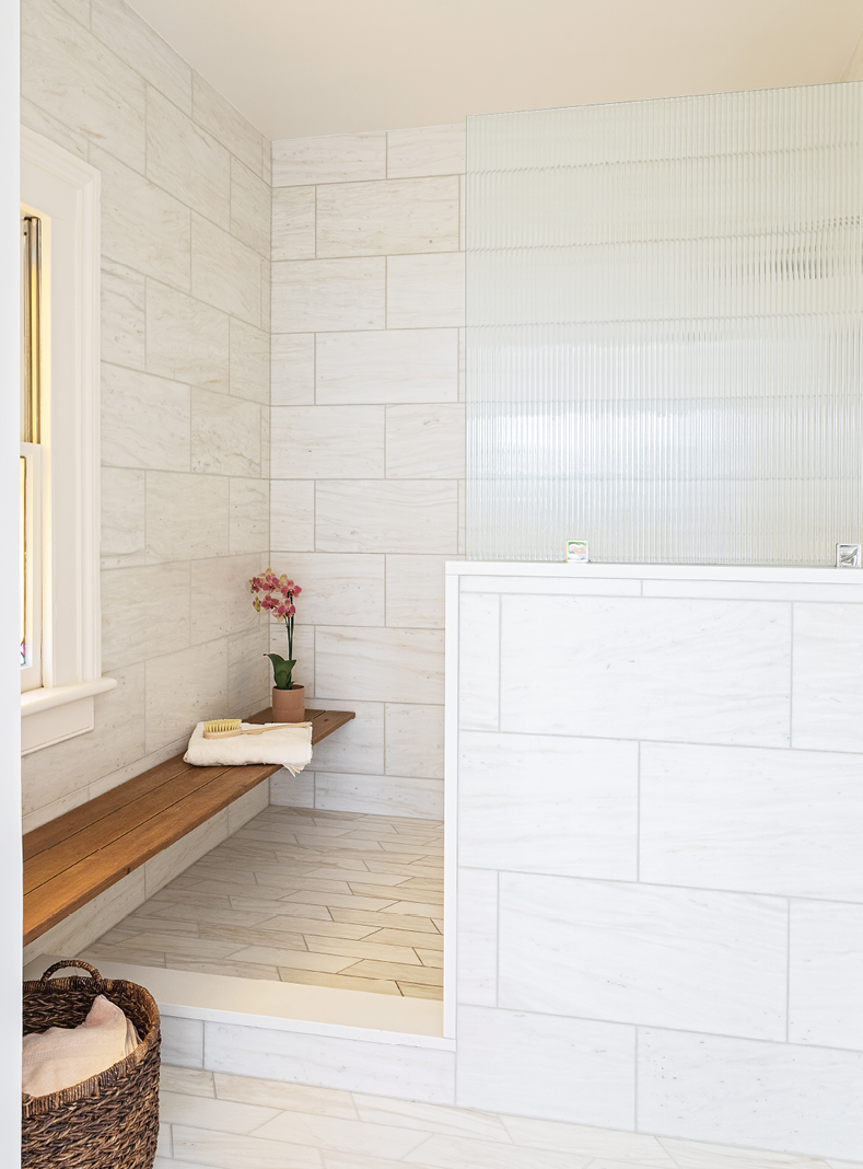 Neutral Territory: A mix of textures, scale, and tone in the tile make this long, lean en-suite bathroom an elegant retreat.