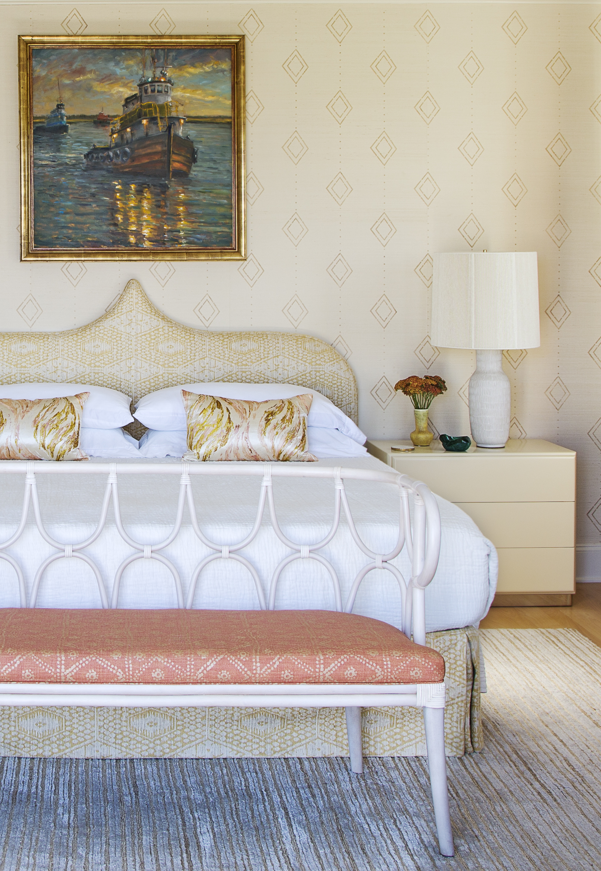 """As the downstairs primary bedroom was converted to a den and home gym, this second-floor suite received full posh treatment, including Allen's gold hand-stenciling on a grasscloth wall covering, a first for Hranowsky. The diamond pattern is echoed in the headboard and bed skirt fabricated in a jacquard silk by Jennifer Shorto and bench found at 1stDibs and recovered in Carolina Irving Textiles """"Zig Zag"""" fabric in """"coral."""""""