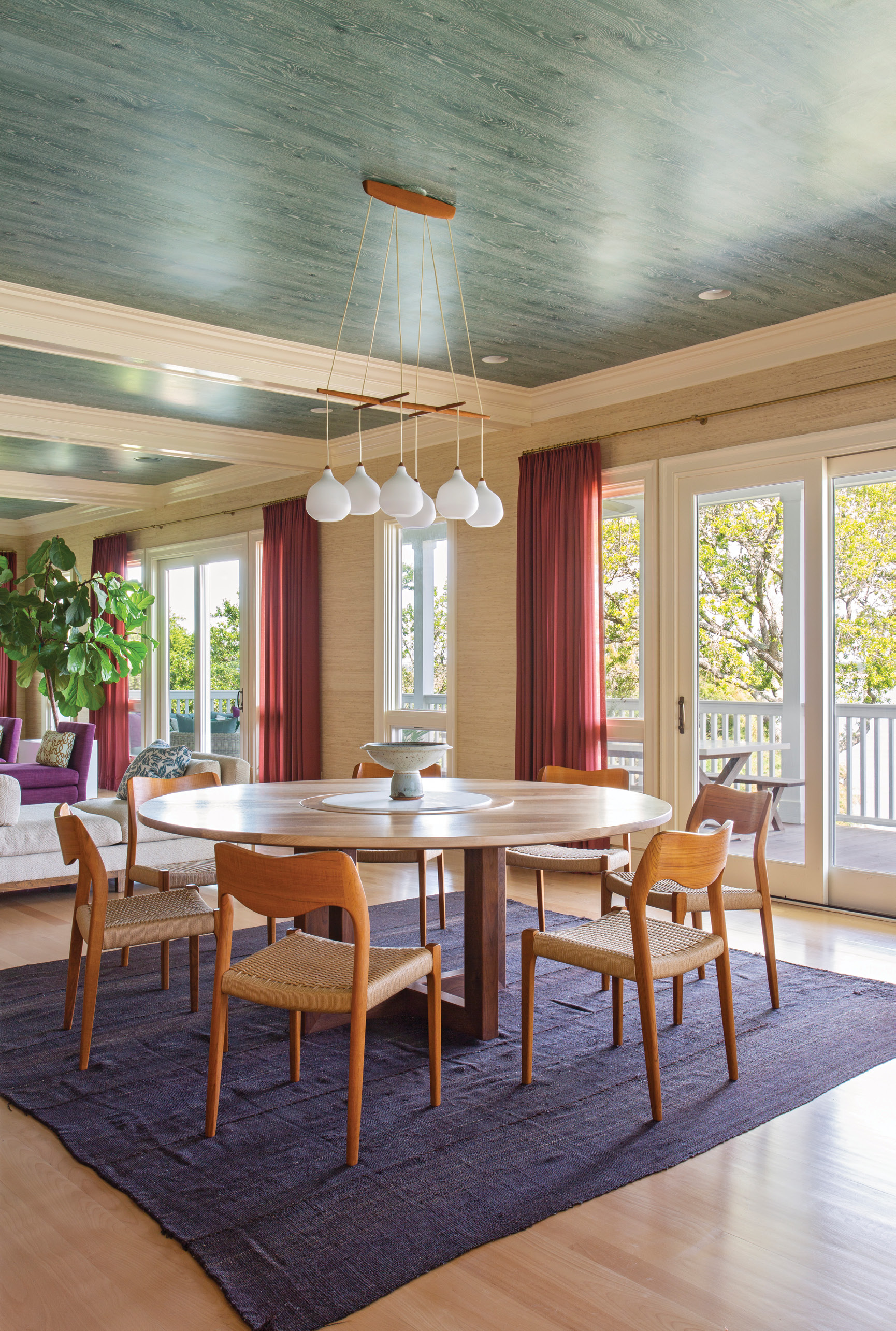 """""""A round table was definitely called for here,"""" says Hranowsky, who was seeking to balance the kitchen's linear shapes. Her carpenter custom created the walnut dining table, outfitted with a marble lazy Susan that was Phil's engineering. A vintage Danish teak and white glass chandelier from 1stDibs adds casual spunk to the dining room without obstructing views into the kitchen or out to the waterway."""