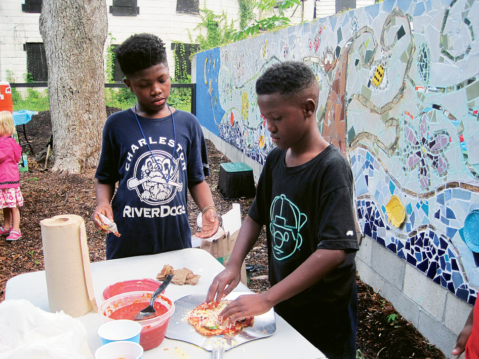 Young pizza-partiers make pies to slide into the cob oven that was built by architect April McGill and mosaicked by artist Meryl Weber.