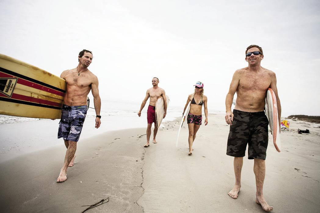Chris Brown, Luke Pope-Corbett, Jenny Brown, and Chris Dixon walk along beautiful Sandy Point.