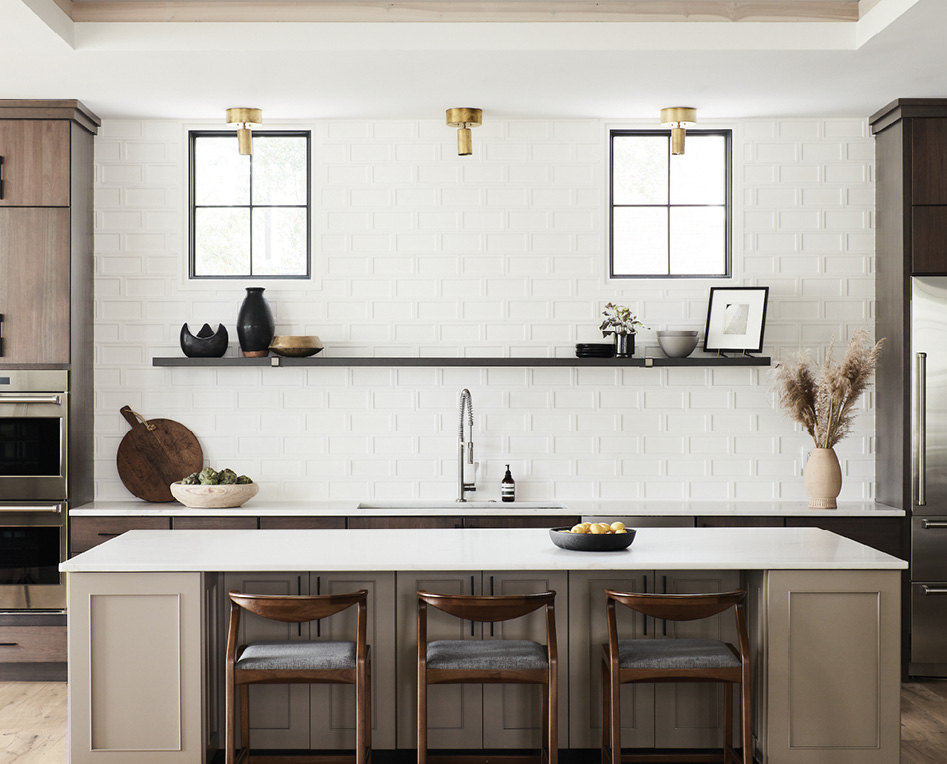 Clean Lined: The kitchen continues the industrial-modern vibe. Unlacquered brass light fixtures with an oversized canopy were designed by Jones to complement the Lyptus wood cabinets in a slate ebony finish while contrasting with the white tile