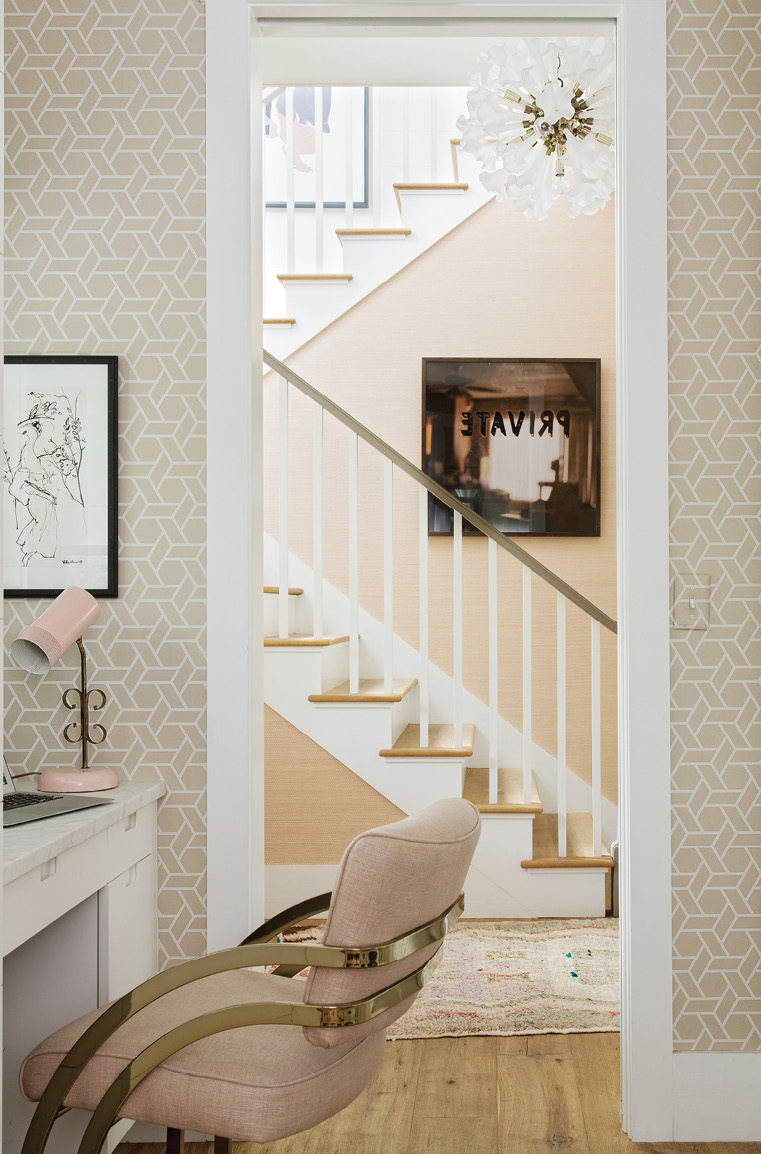 Corner Office: Tucked in the laundry room/butler's pantry, Jenny's home office features whimsical wallpaper by Cowtan & Tout, a mid-century French lamp, and a favorite Slava Roubanov sketch from Charleston Artist Collective. The adjoining hallway showcases a vintage chandelier from 1stdibs and Mona Kuhn's Private from Jackson Fine Art in Atlanta.