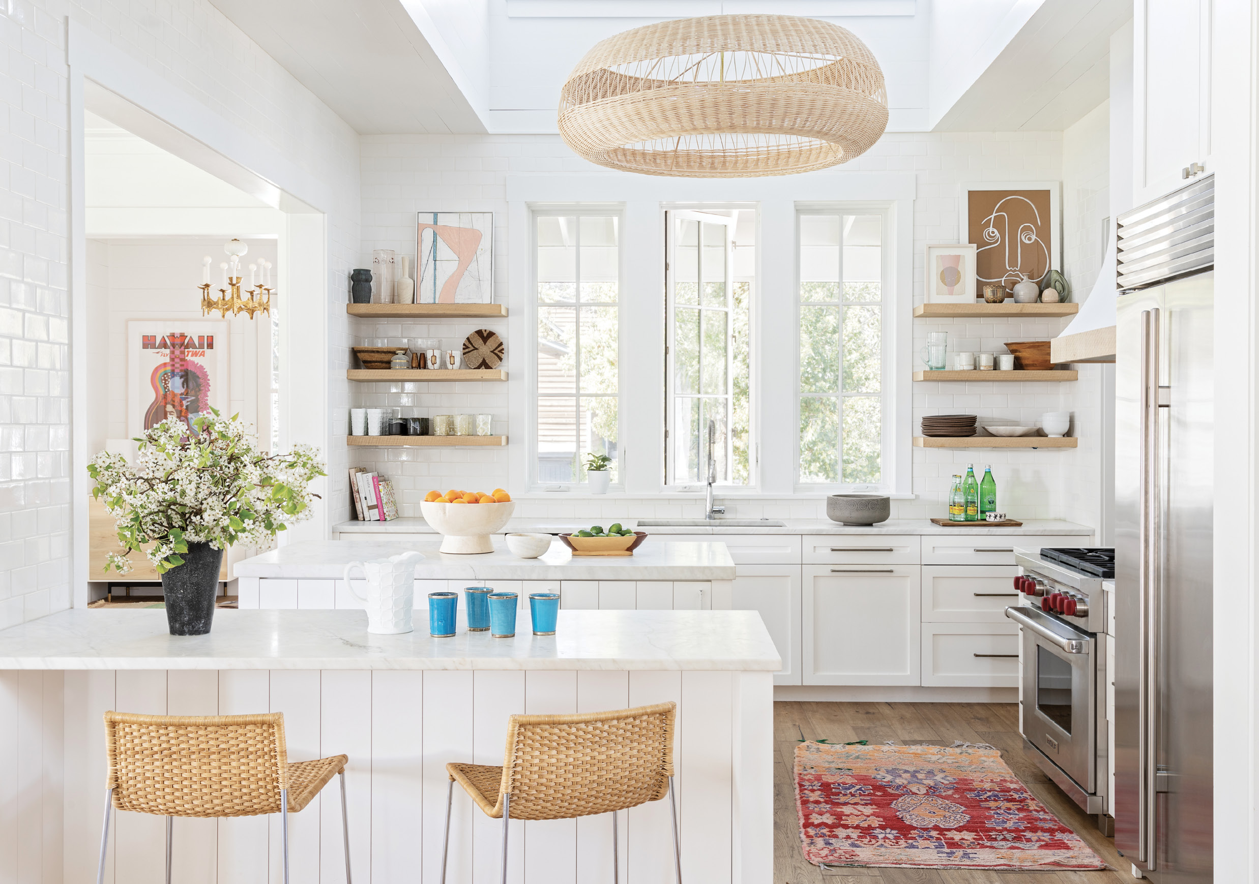 TIME FOR TEXTURE: The bright, white kitchen was revived with some key texture changes: wooden shelves replaced painted ones and a stainless steel hood was swapped for plaster trimmed in oak.