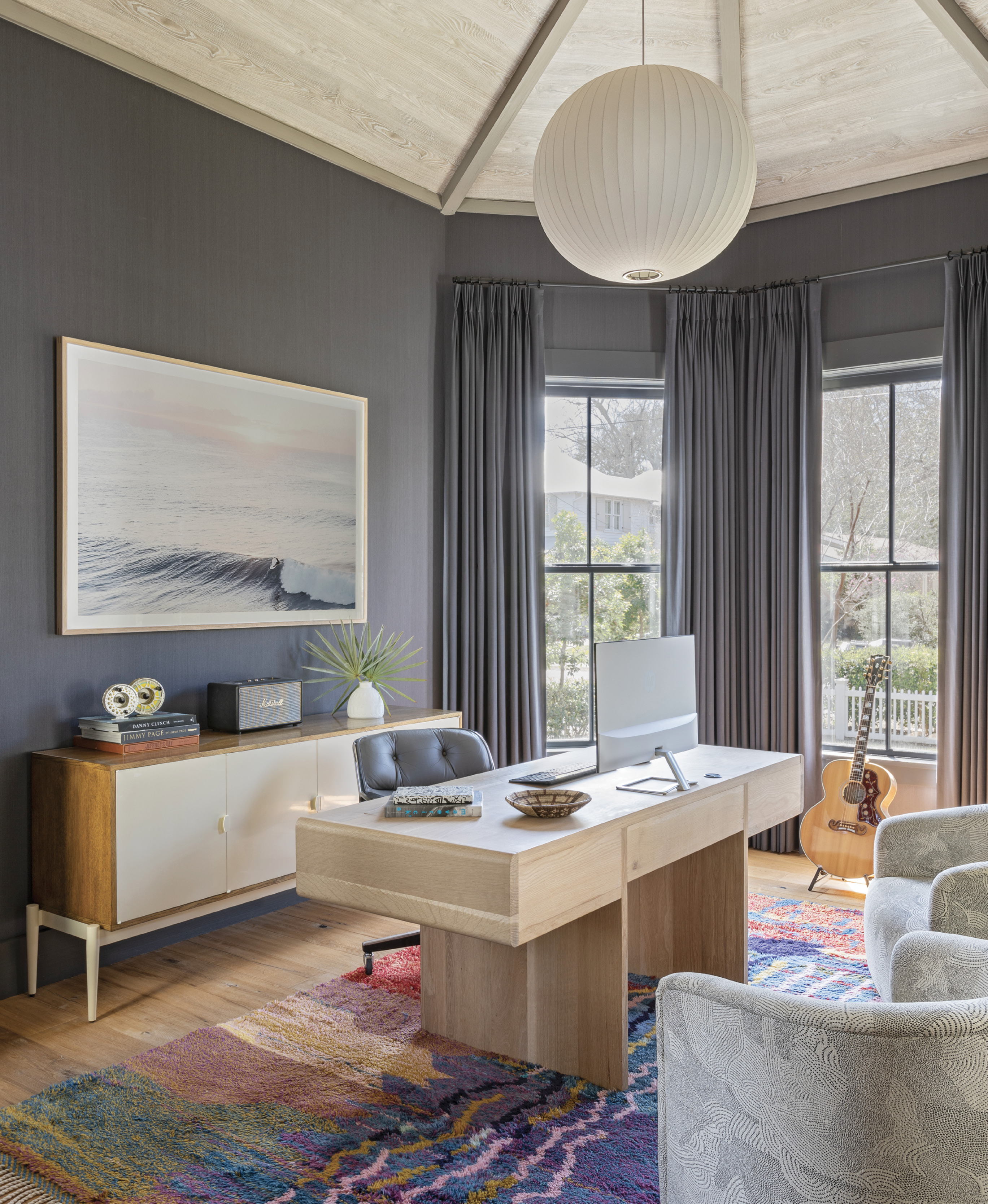 "ZOOM ROOM: The octagonal dining room saw little use pre-pandemic, so Jenny turned it into a handsome home office for her husband, Joe. Inky blue Phillip Jeffries grasscloth wallcoverings and drapes fashioned in Romo washable linen in ""Linara Blueberry"" set a dramatic yet soothing backdrop for the custom white oak desk by carpenter Ryan Mckiernan, vintage Baker Furniture sideboard, and Kate Holstein photograph of Maui's Honolua Bay from Mount Pleasant's Heart of Gold Gallery."