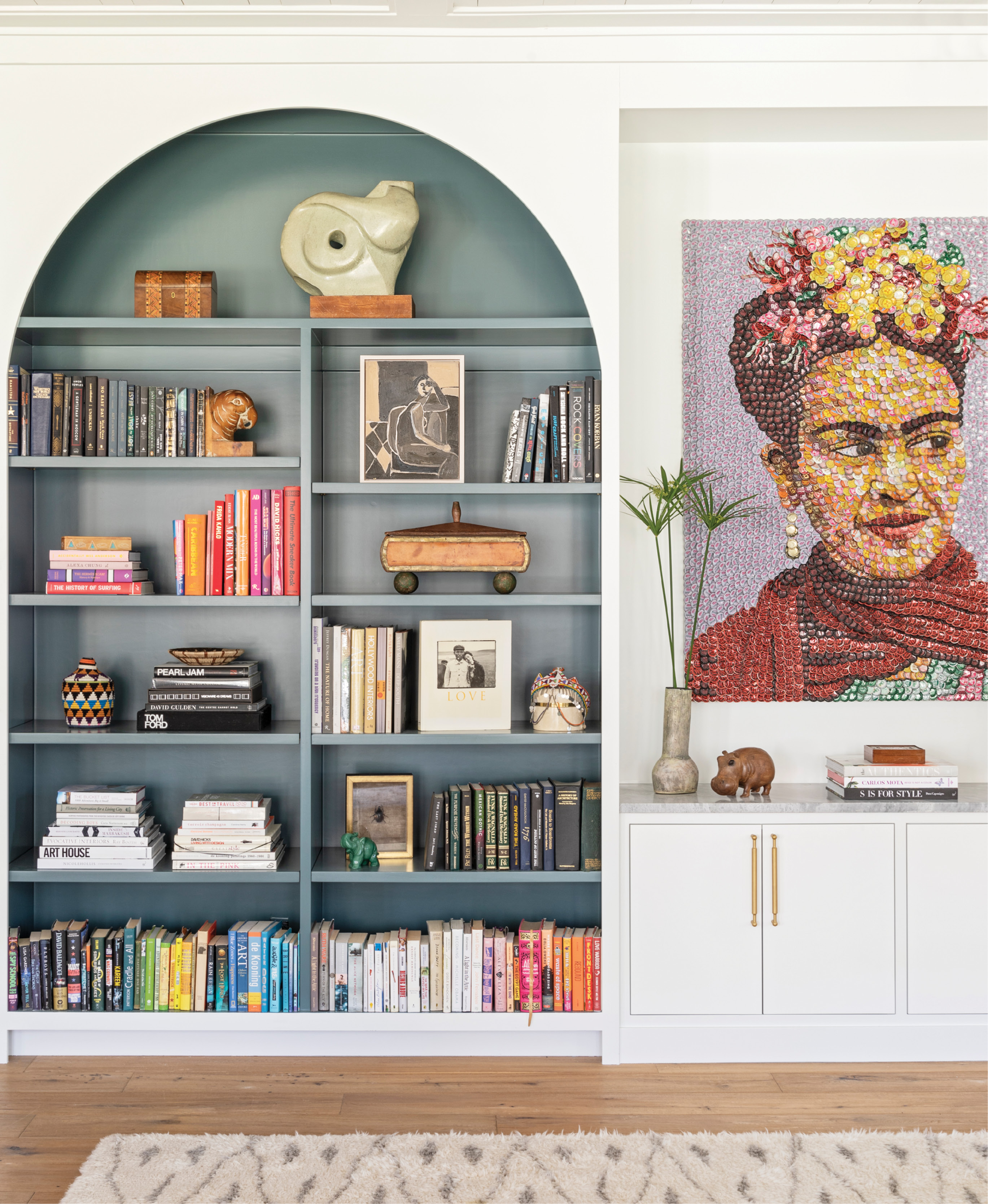 "Top Shelf: Adding built-in bookshelves to the living room brought order to the room while providing a pop of color courtesy of Farrow & Ball's ""Inchyra Blue."" The custom design also beautifully showcases local artist Molly B. Right's bottle-cap homage to Frida Kahlo. A brass and wicker side table from Hollywood at Home and vintage shearling chair from 1stdibs add texture and dimension."