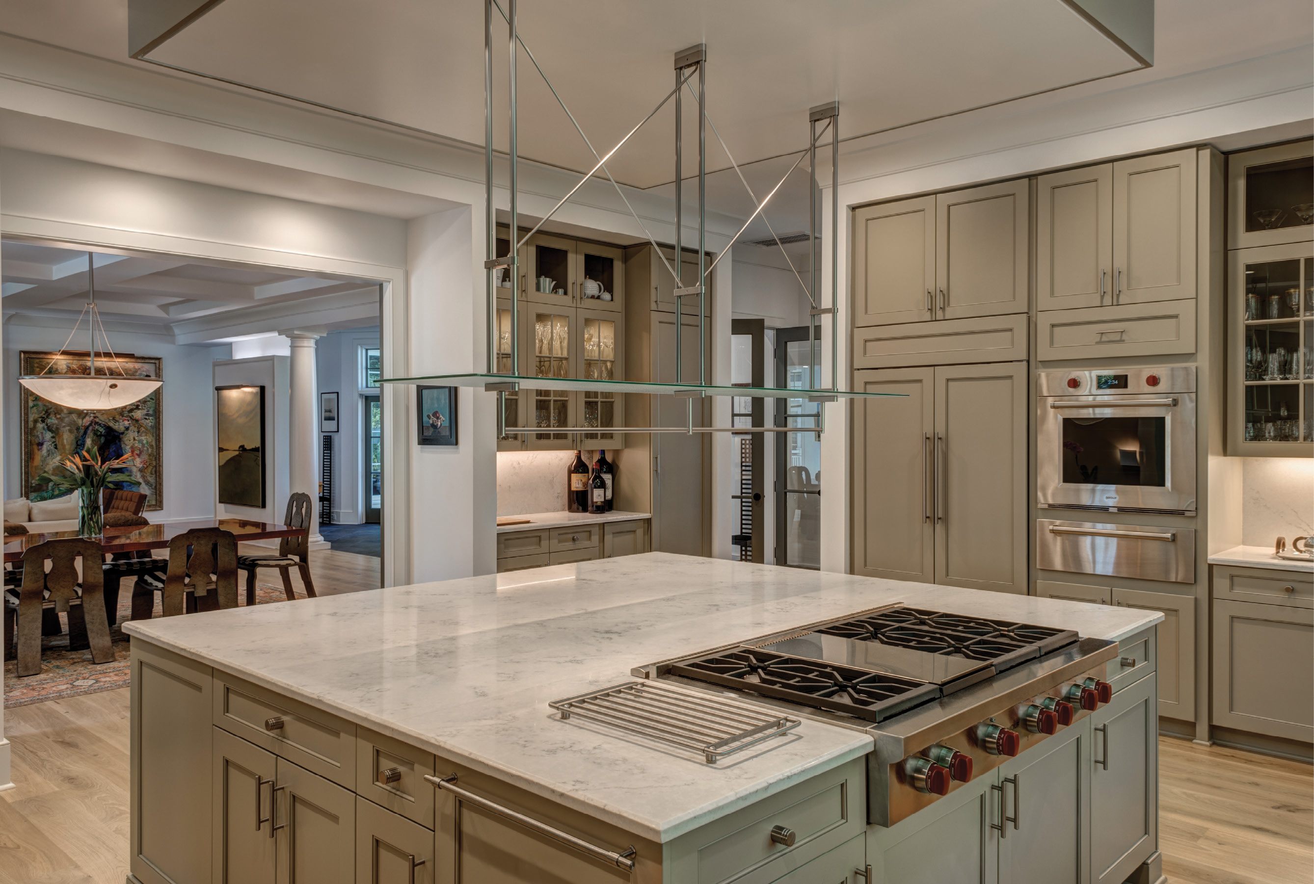 "COOKING LIGHT: Abundant natural light is the main ingredient in the spacious kitchen, where an oversized island with quartz countertops offers a central gathering space. ""We entertain a lot,"" says the wife, who loves to cook but gives her husband props for ""approaching chef status"" with his culinary expertise."