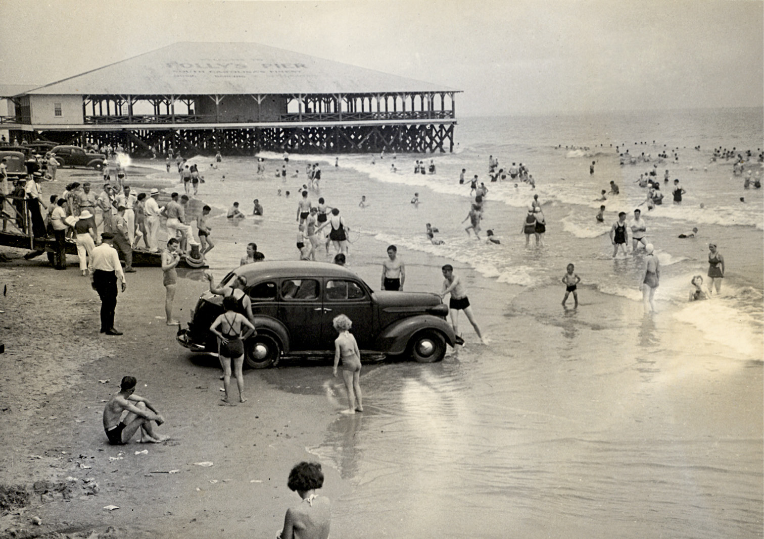 A car parked on the beach gets caught in the incoming tide, circa 1950.