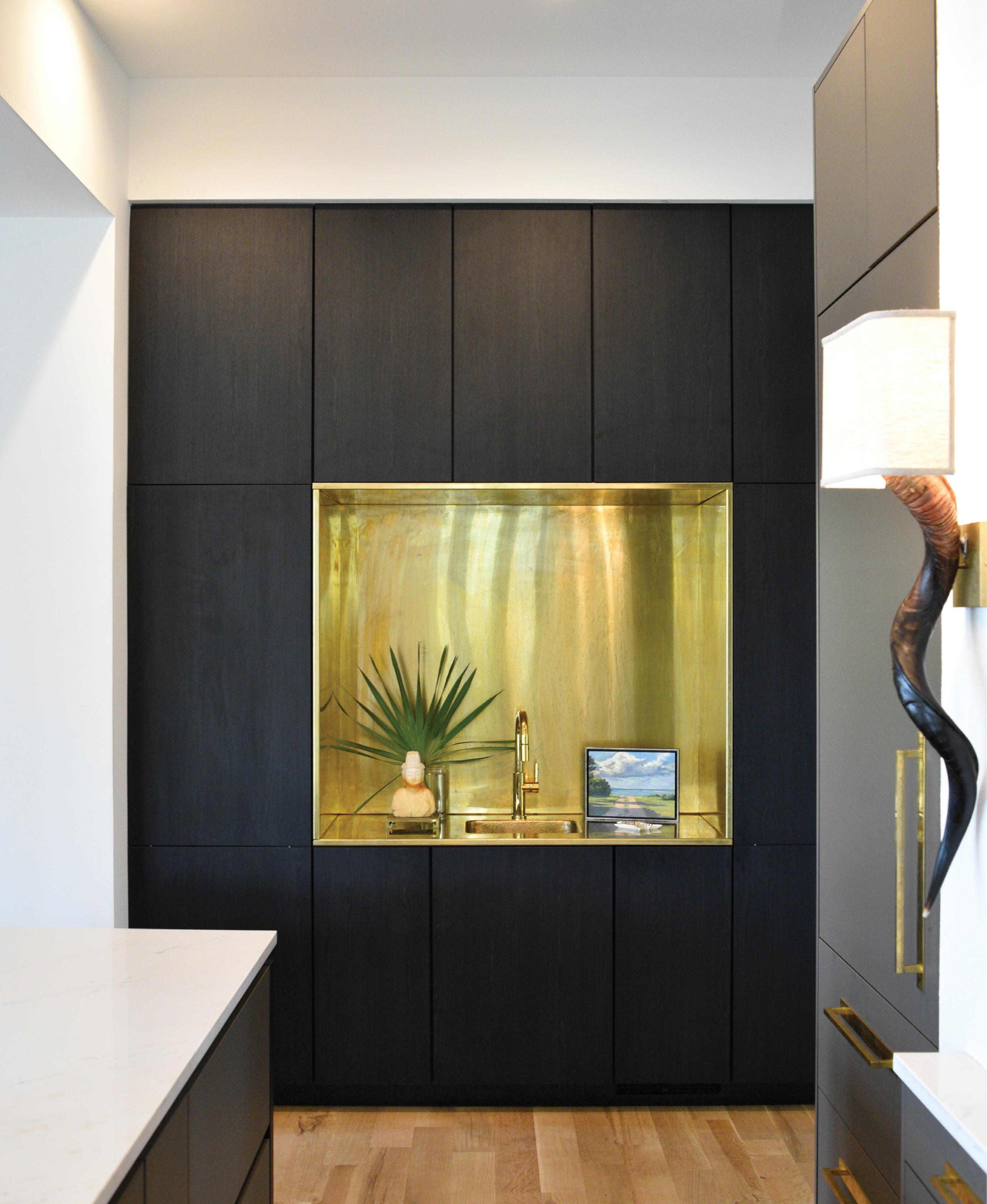 This unlacquered brass wet bar, fabricated by Mount Pleasant metalworker Jon Mako, adds a warming graphic element to the dramatic kitchen.