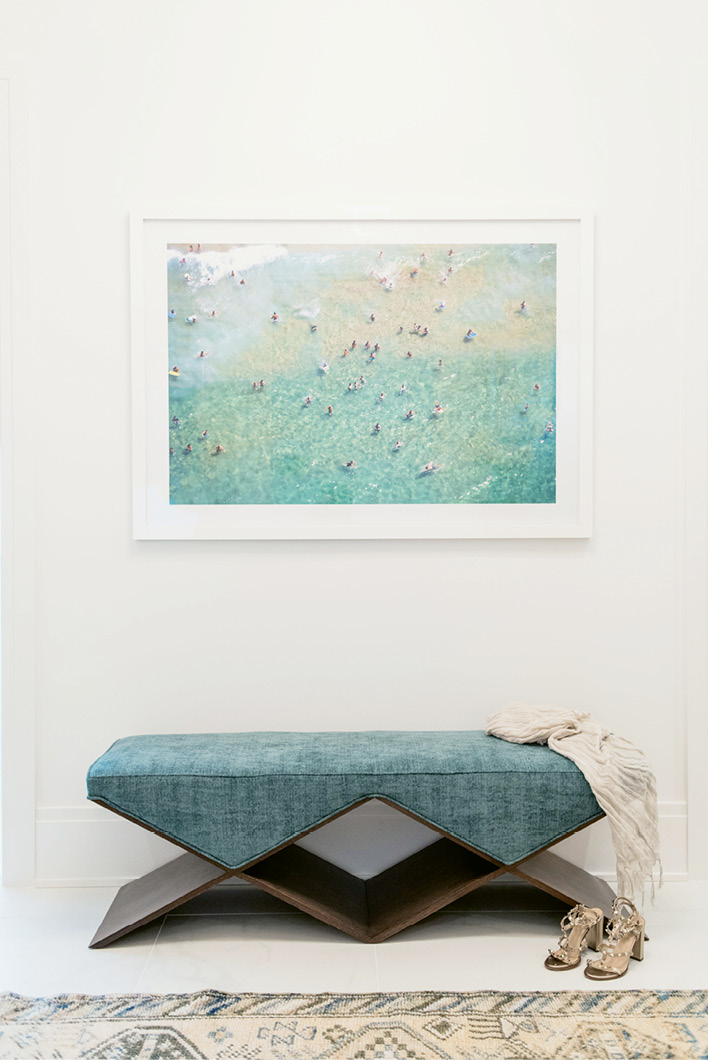 An angular, custom-designed bench (over which a coastal scene snapped by Gray Malin hangs) add modern style in spades.