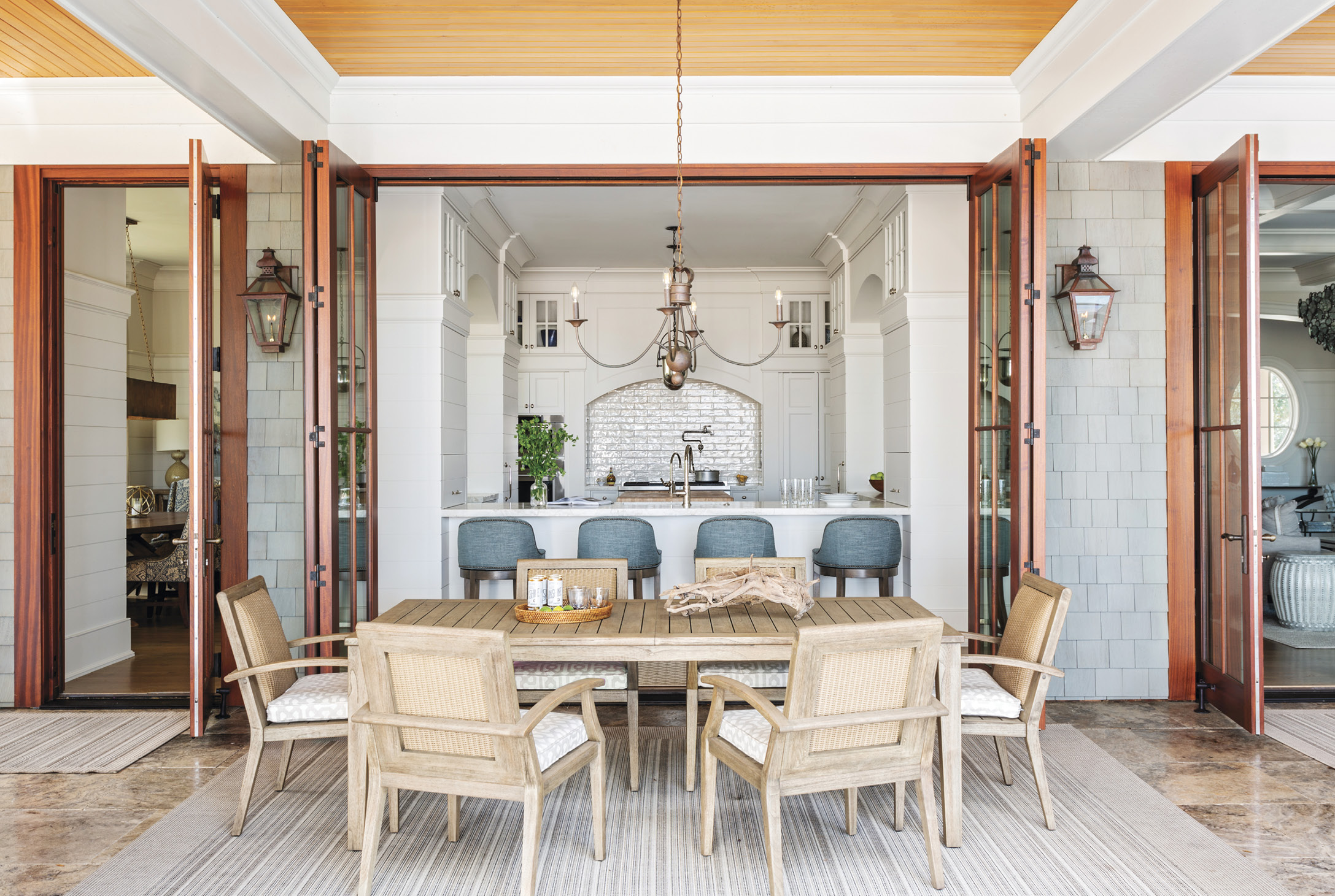 EATING IN & OUT: A floating kitchen anchors the home, tying the indoor and outdoor living spaces together. The alfresco Lloyd Flanders dining table and chairs, purchased at GDC Home, is as accessible to the chef as the formal dining room.