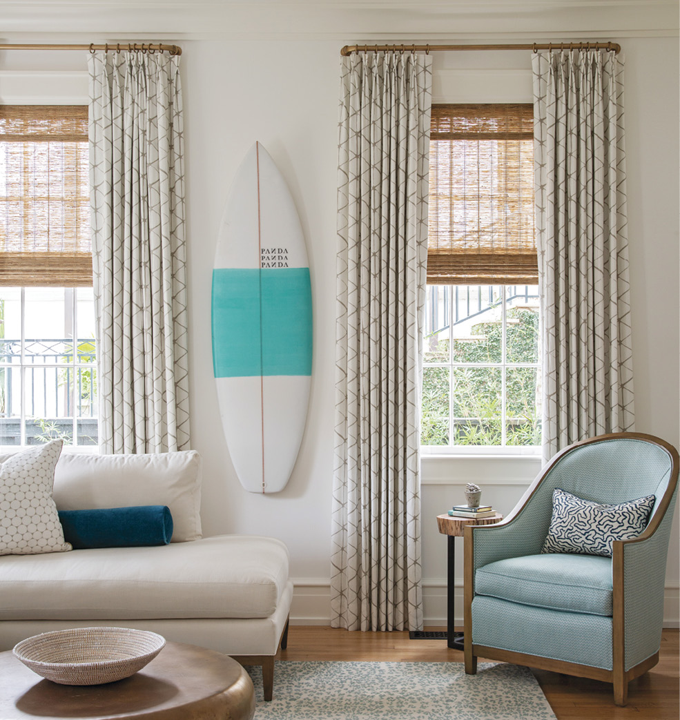 The voluminous drapes, also in Villa Nova fabric, bring warmth and texture to the walls, where a PANDA surfboard nods to Hugh's passion for the sport.