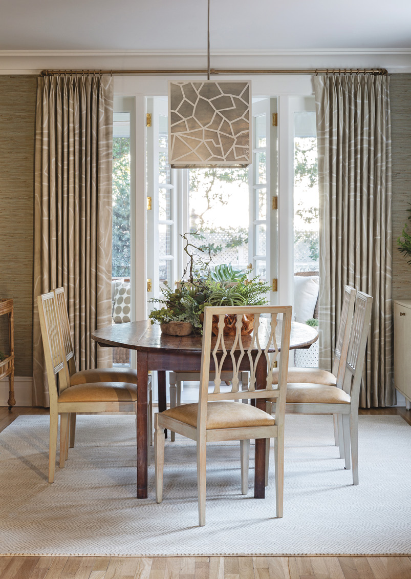 Just inside, the dining room's grasscloth wall covering from Kravet lends an earthy, outdoorsy feel to this elegant space, which welcomes in even more natural light thanks to a window relocated from the master suite.