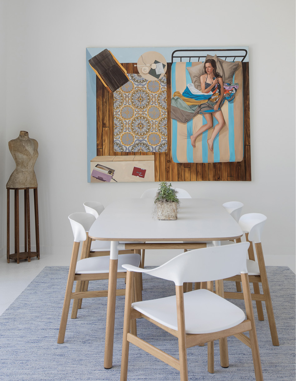 "SMALL TOWN CONNECTIONS: Baldwin recently hosted a dinner party around this Normann Copenhagen dining table and chairs and commented that a guest at the end of the table looked just like the young woman in the Netflix painting by Karen Ann Myers hanging above. ""That's her,"" came the reply."