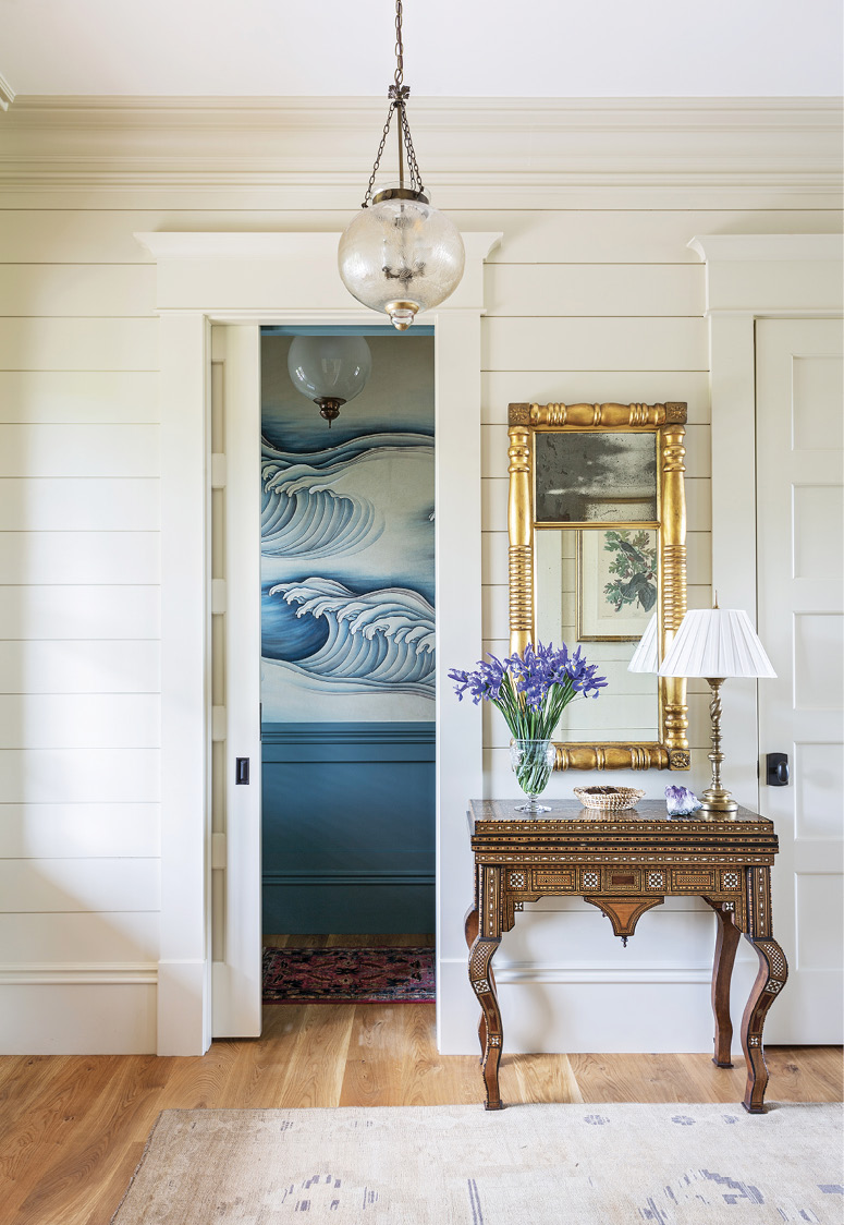 A WAVE THROUGH TIME: A bold blue and white hand-painted wallpaper from Gracie evokes the home's nautical theme in the downstairs bathroom, while Martha's grandfather's exquisite 1920s Indian game table greets guest in the entryway.