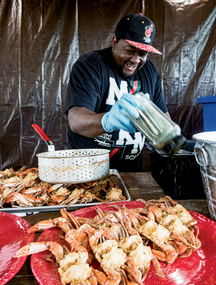 "For a gathering at Lady's Island Oyster Farm, Louis ""Granny"" Albany shakes spices onto local blue crabs."