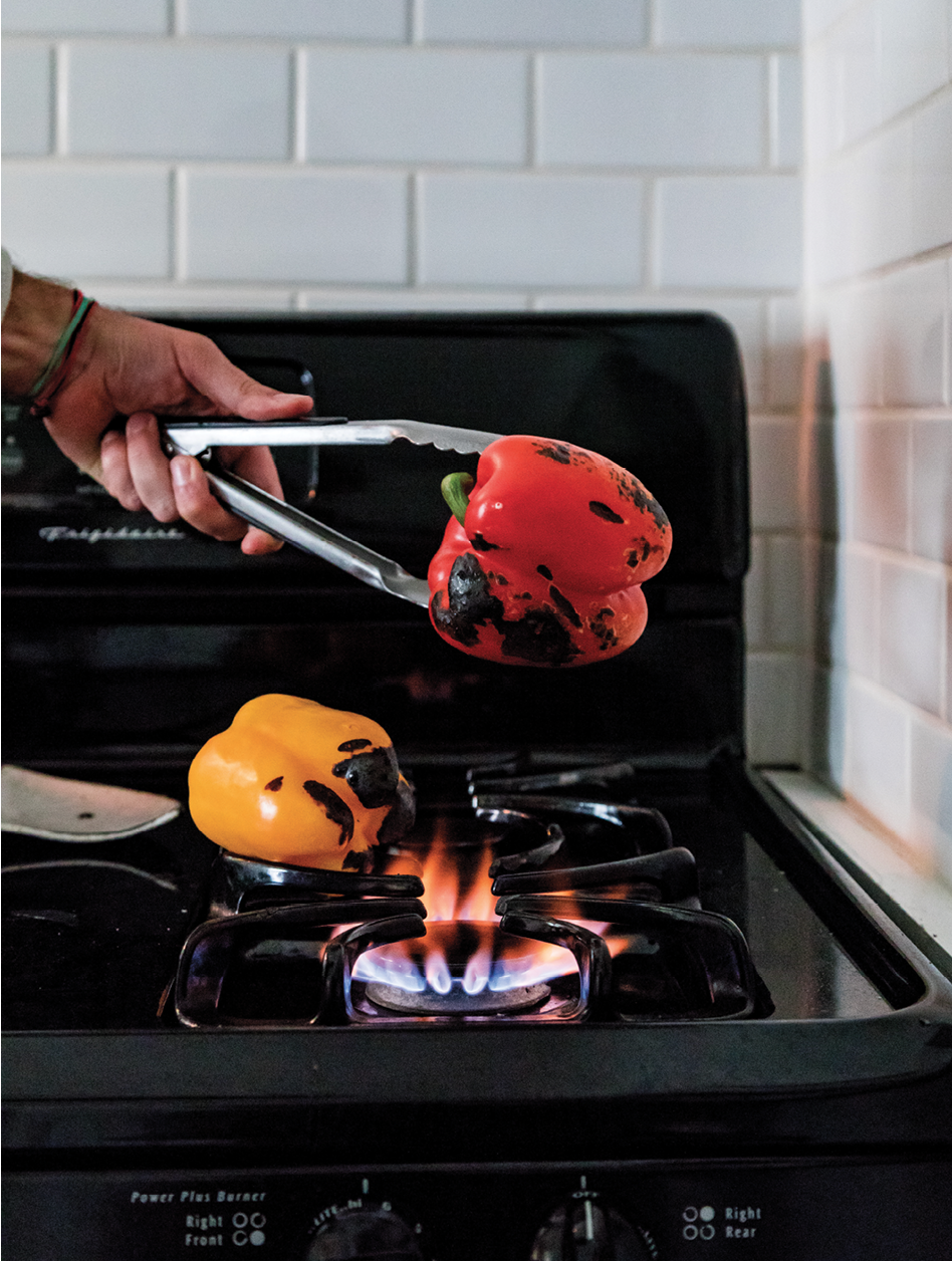 Reitz roasts peppers over an open flame, turning constantly, until they're charred on all sides.