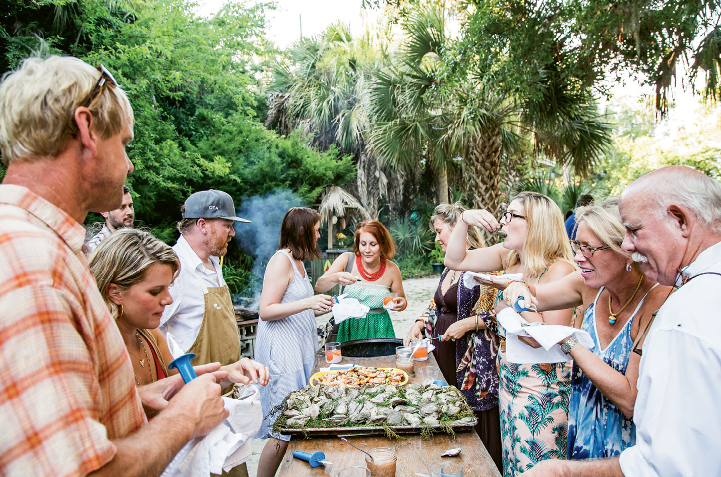 Guests peel shrimp and pry open juniper-roasted oysters only moments after Deihl pulls them from the fire pit. An evening breeze rustles the nearby juniper tree from which the garnishing sprigs were clipped.