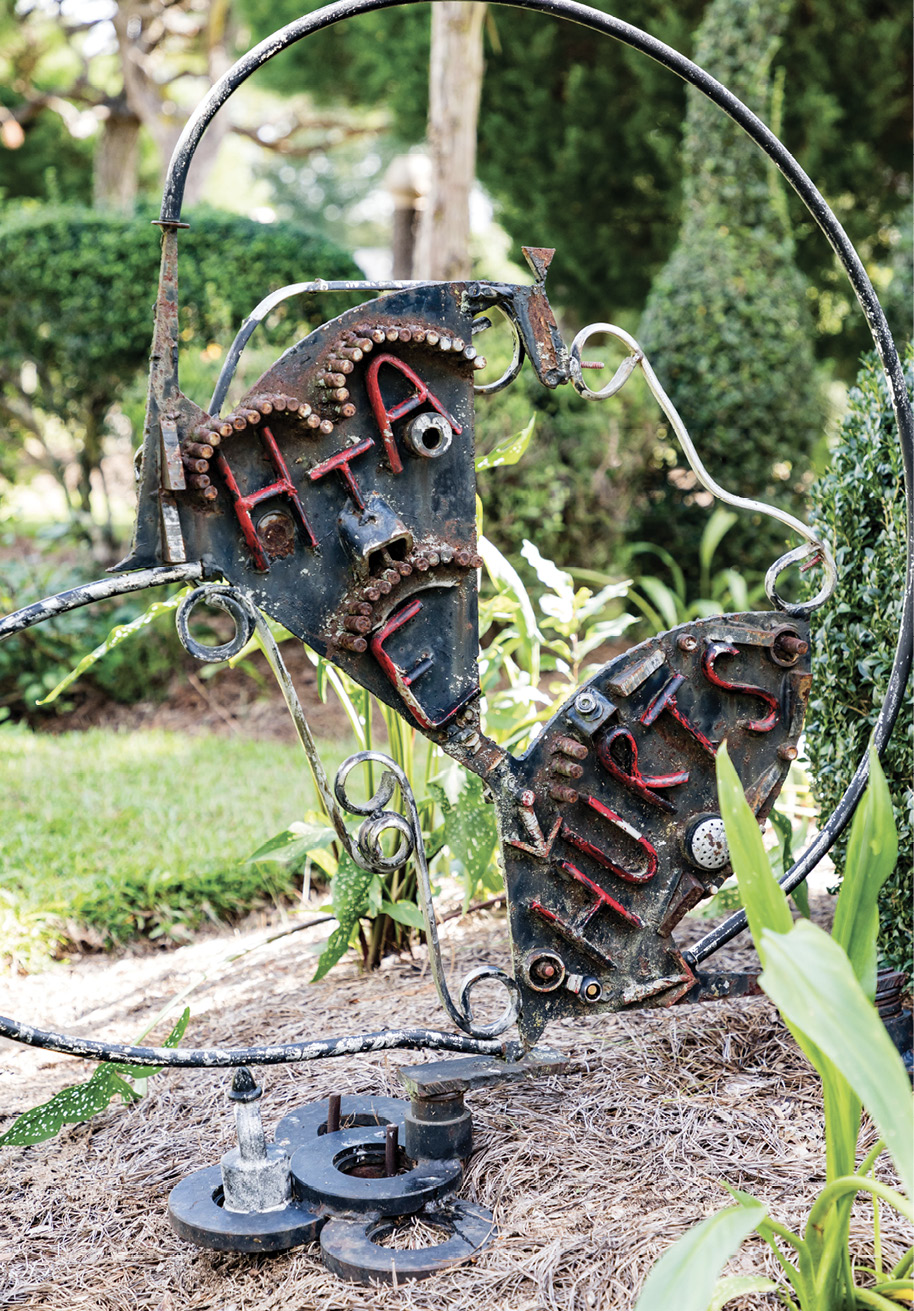 "WORDS OF WISDOM: Over the years, Fryar has added more fabricated sculptures as counterparts to shrubs and trees. He uses metal pieces, pottery, bottles, and other found objects. Sometimes he adds lettering, such as for the metal sign with ""Hate hurts"" and an arrow pointing downward. The other side reads ""Love and Unity,"" with an arrow pointing upward."