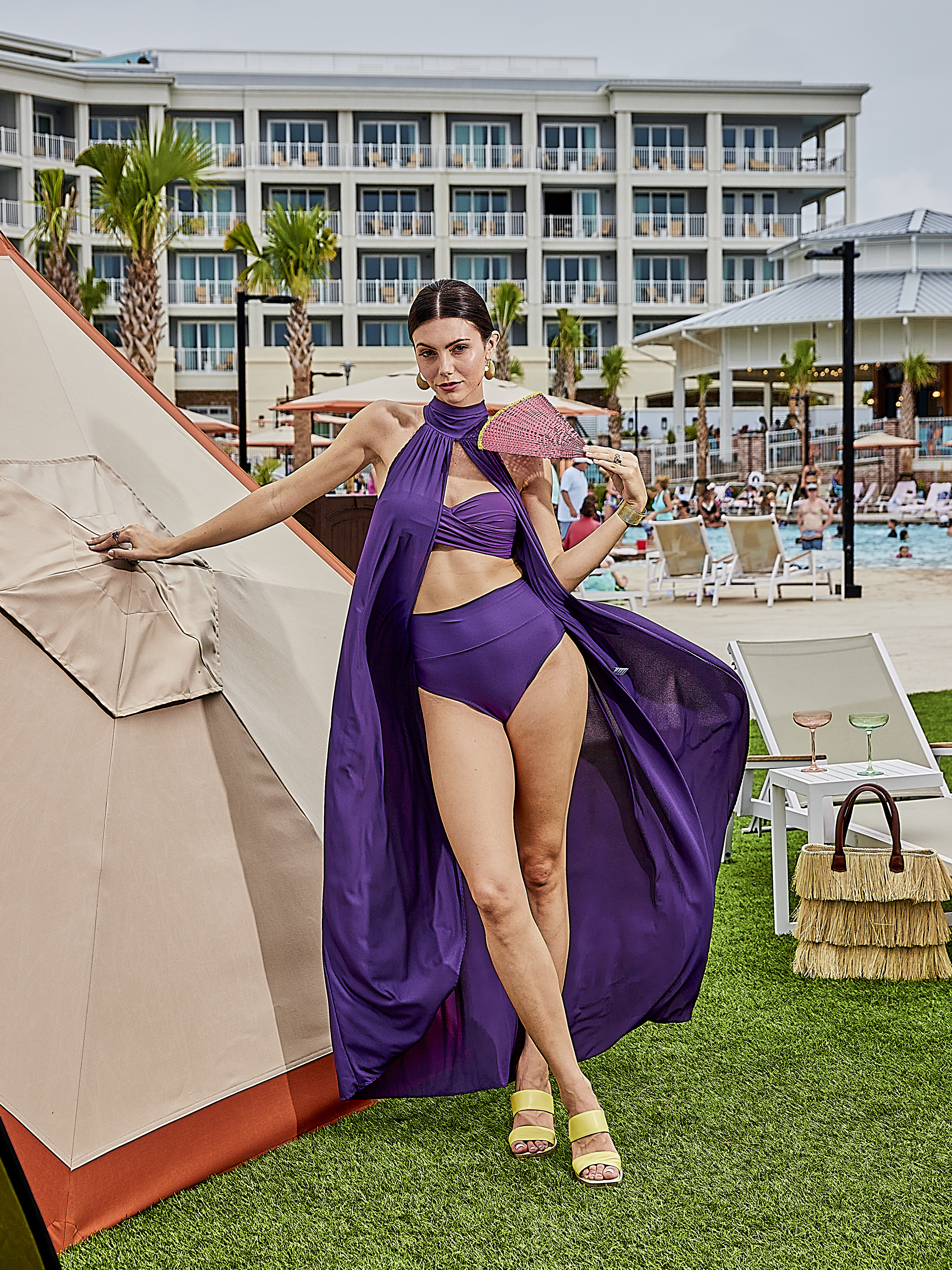 """Purple Reign: Twist-front bandeau, $94, high-waist bottom, $74, and cover-up, $149, all at Tara Grinna at The Shops at Belmond Charleston Place; gold crescent earrings and bangle, $180 each at Seyahan Jewelry; Pe Jay Creations mixed gemstone cluster ring, $1,630, and amethyst fashion ring, $4,880, both at Diamonds Direct; Roberto Coin """"Love in Verona"""" band with diamond accent, $3,500 at M.P. Demetre Jewelers; Anthony Lent eternity band, price upon request at RTW; A.G.L. """"Surin"""" heel, $560 at Gwynn's of Mount Pleasant; fan, $16 at Ibu; Sensi Studio straw bag, $399 at Harper and Hartford; Estelle Colored Glass champagne coupes, $33 each at Gwynn's of Mount Pleasant"""