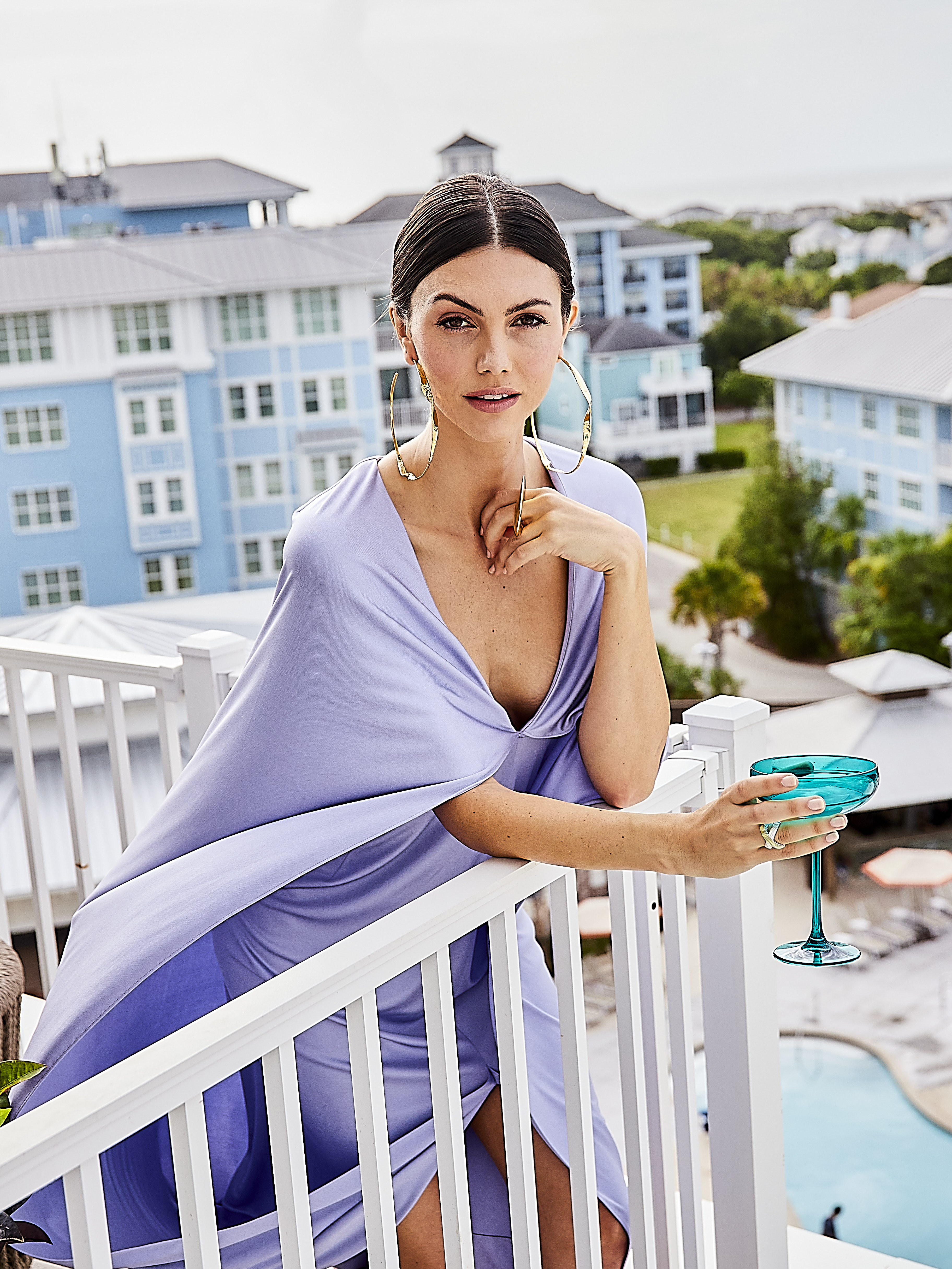 """Go With the Flow: St. John silk jersey dress, $3,495, maxi hoop earrings, $195, and sculpted double ring, $195, at St. John Boutique; Lagos pavé crossover ring, $2,500 at M.P. Demetre Jewelers; Estelle Colored Glass champagne coupe in """"emerald,"""" $33 at Gwynn's of Mount Pleasant"""