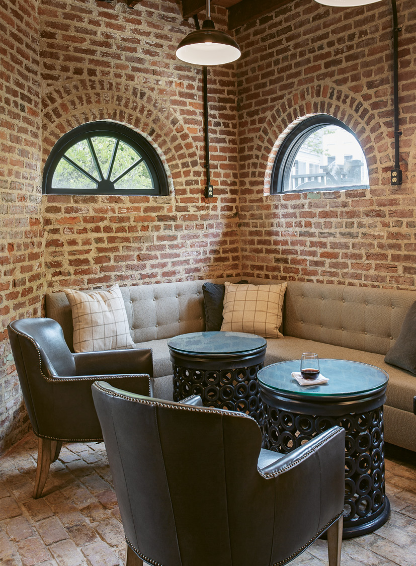 "For this lounge area, designer Kristin Peake echoed the motif with cylindrical side tables, spinning barstools, and round mirrors to soften the hard lines of the floorplan and exposed brickwork. See the electrical outlets mounted on the walls? That's another flood-proofing trick to prevent inevitable storm surges from wiping out wiring that runs along ground level. There's no insulation on the bottom three feet of this floor. ""It's all brick, which can take the water,"" says Rick. ""We'll just pump anything out."""