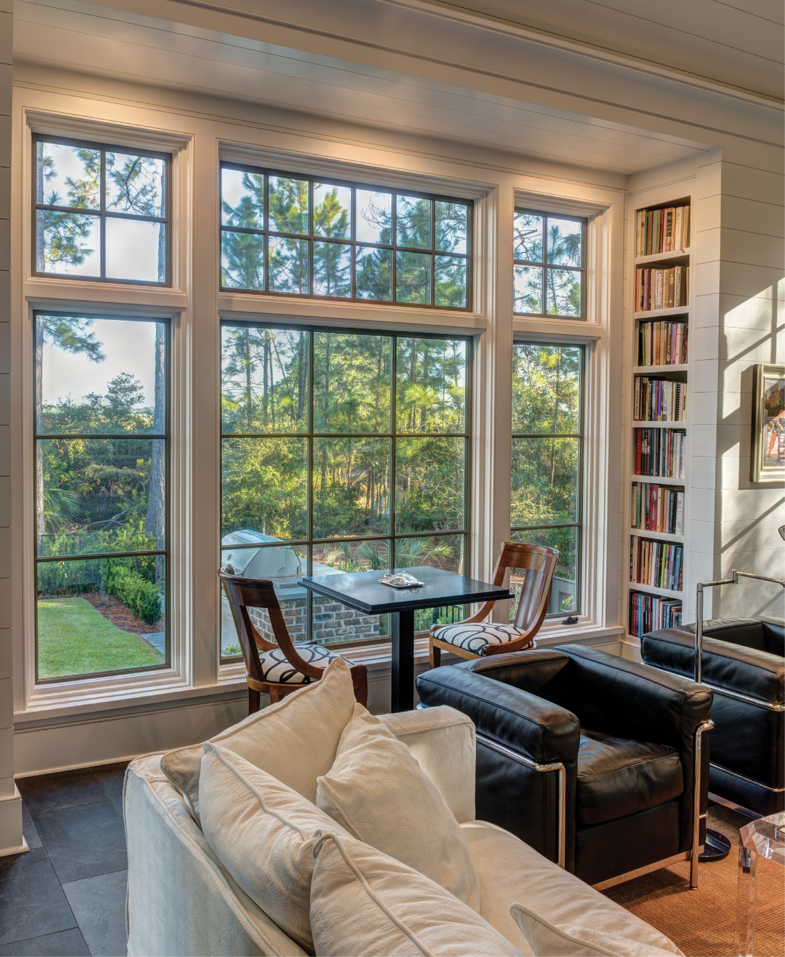 A STUDY IN CLASSICS: Outfitted with shiplap walls, bluestone flooring, and select furnishings by Baker and Ralph Lauren (many designed by architects), the library features a cozy fireplace, plus a wall of custom built-ins.