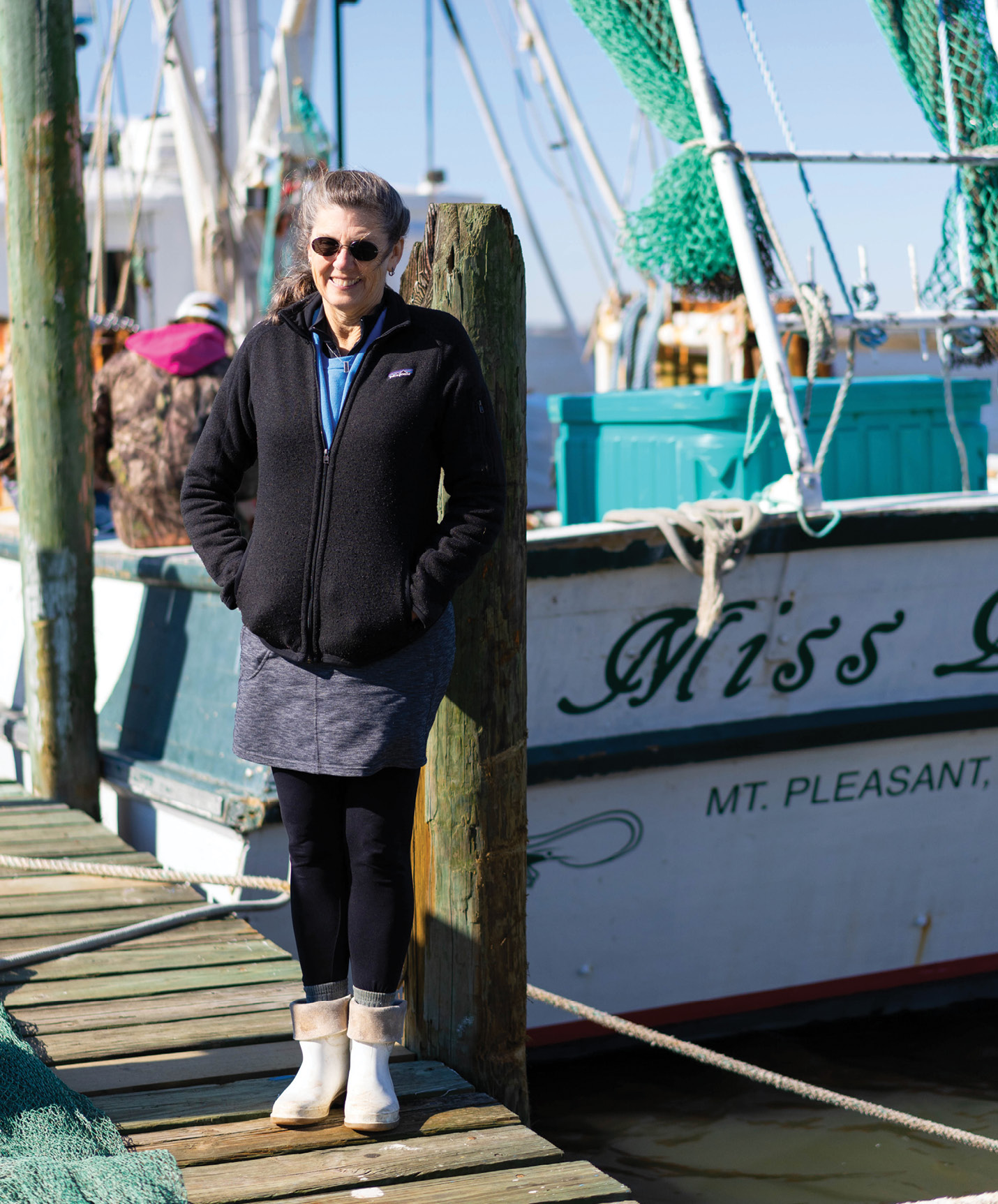 Cindy Tarvin beside the classic wooden trawler that she and her husband bought in late 2011