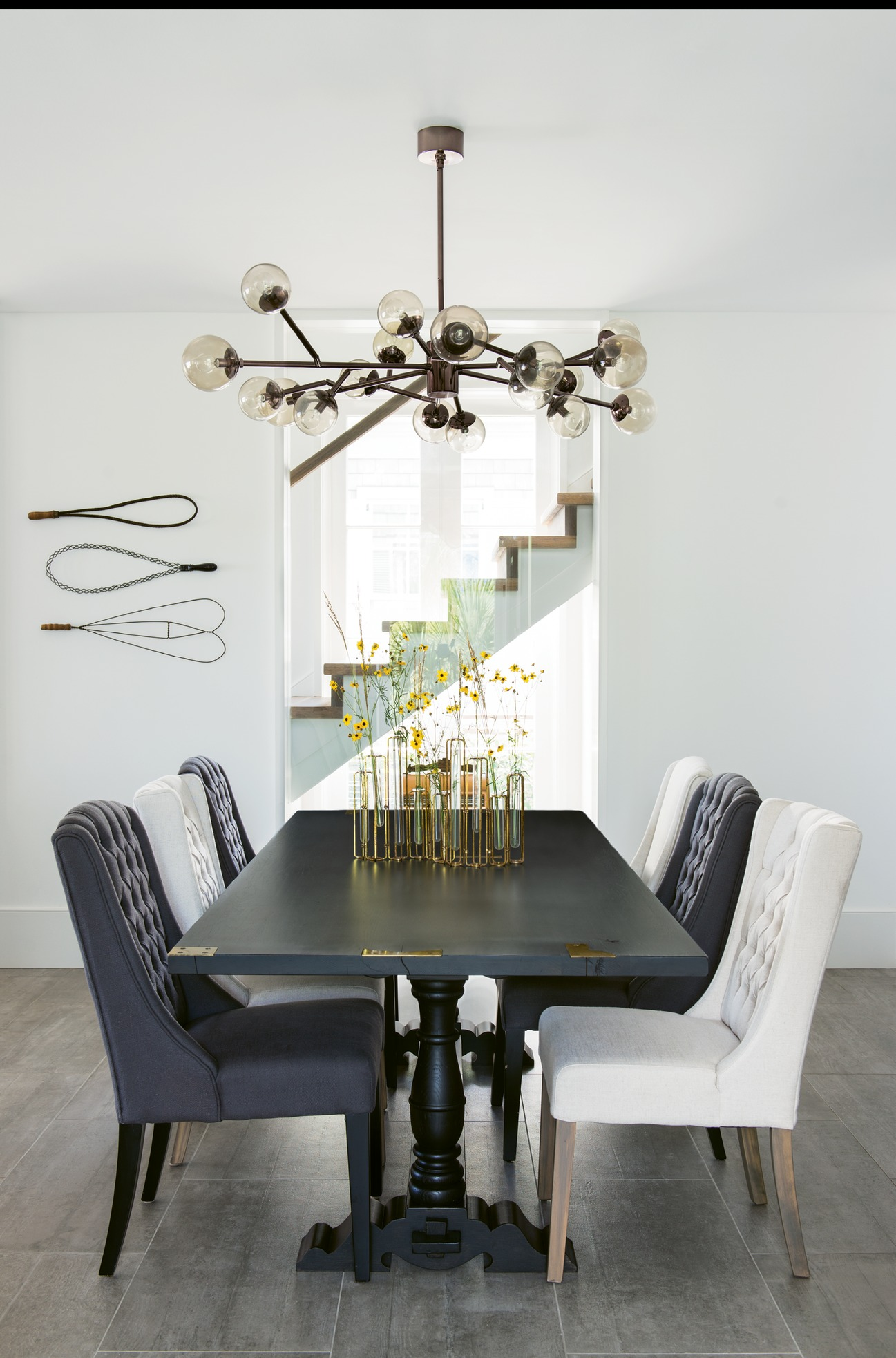 "The couple commissioned cabinetmaker William C. Pritchard to produce a wooden table similar to one they had admired in the Hudson Valley. The upholstered chairs are from ABC Carpet & Home, the mid-century-inspired ""Dallas"" chandelier from Arteriors."