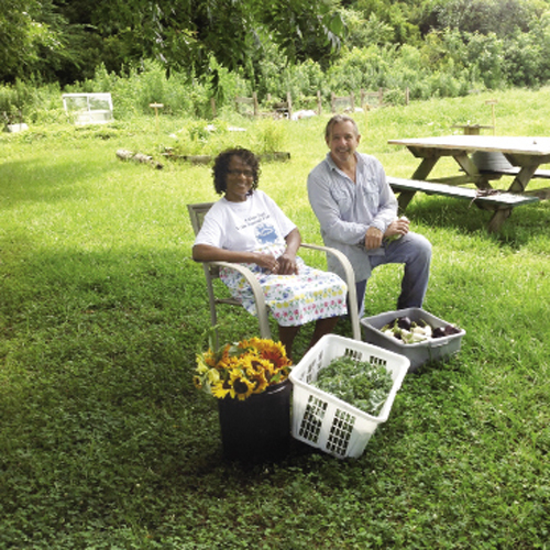 A volunteer collects goods from Sweetgrass Garden farm manager Dale Snyder (right)