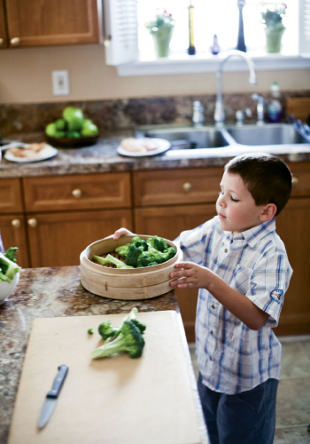 Veggie Tales: Christian pitches in by arranging the chopped broccoli in a bamboo steamer tray.