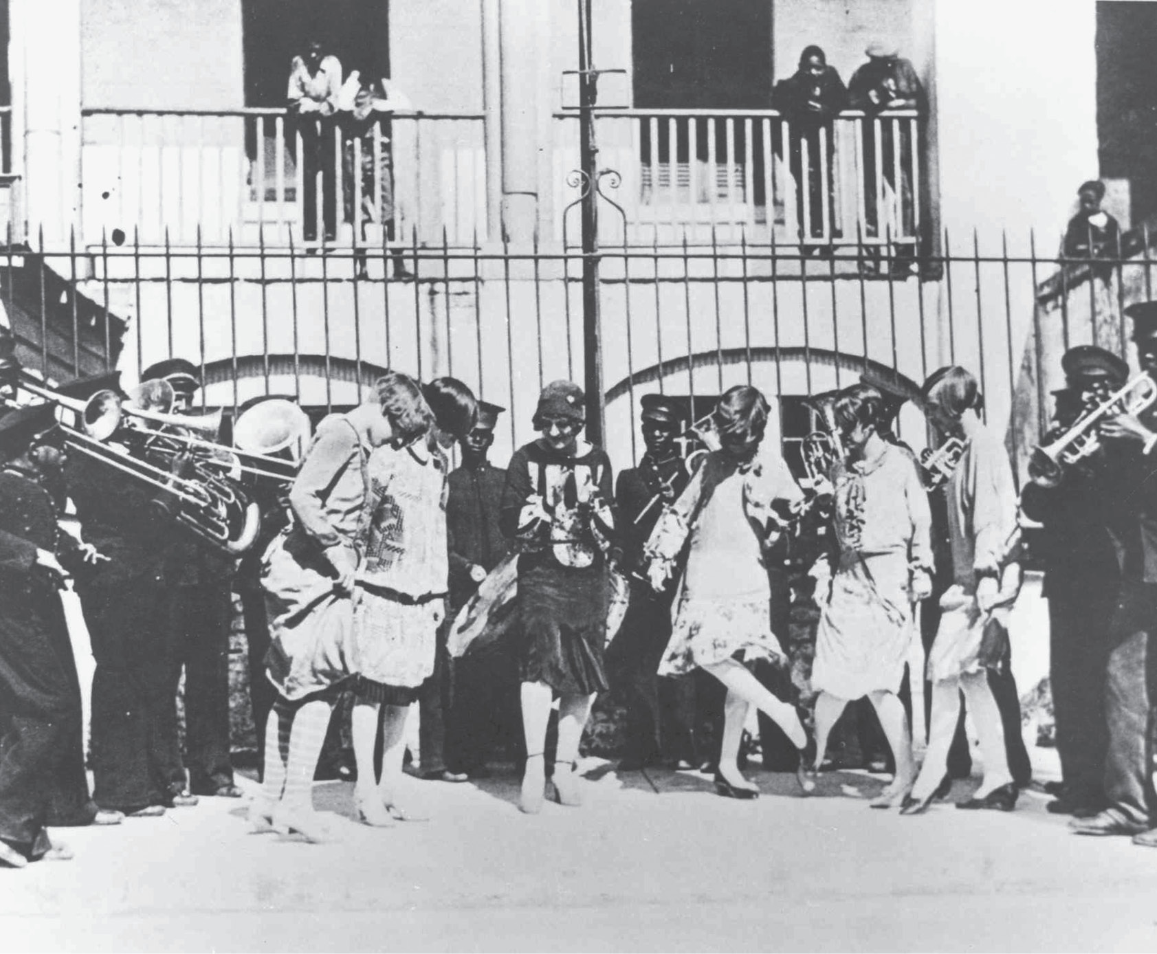 "A group of flappers doing ""The Charleston"" alongside the Jenkins band outside the orphanage on Franklin Street, circa 1920."