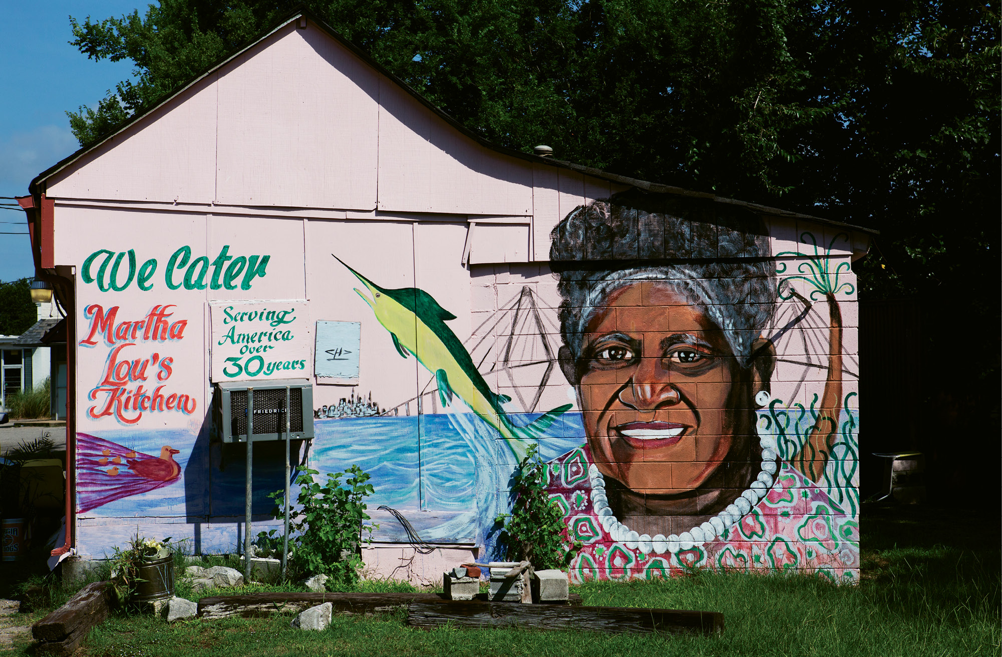 Untitled  by Charles Desaussure  2012  Martha Lou's Kitchen  (1068 Morrison dr., Peninsula)  for decades, locals and visitors alike have sought out the famous pink cinder-block building for the addictive fried chicken inside. in 2012, the colorful exterior got an upgrade, an immense portrait of Martha Lou herself, painted by late Lowcountry artist Charles Desaussure, who passed away the following year. His work can be found on and in many area businesses, including Ravenel Seafood and Red Piano Too Art Gallery in St. Helena.