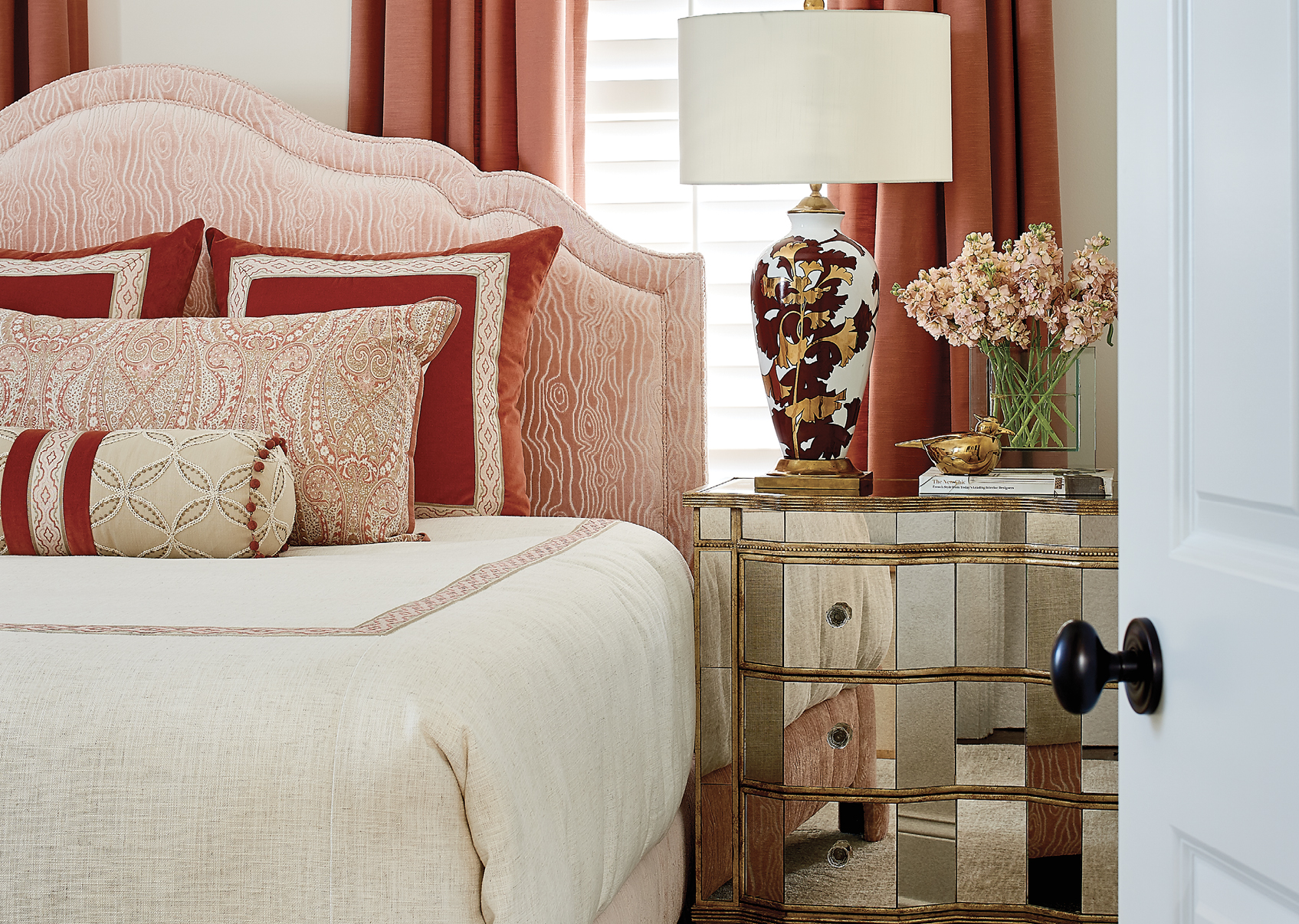 In contrast, the guest bedroom is a cacophony of cheerful colors, with deep peach drapes, a mirrored antique nightstand, and an elegant gold and crimson lamp from Currey and Company.