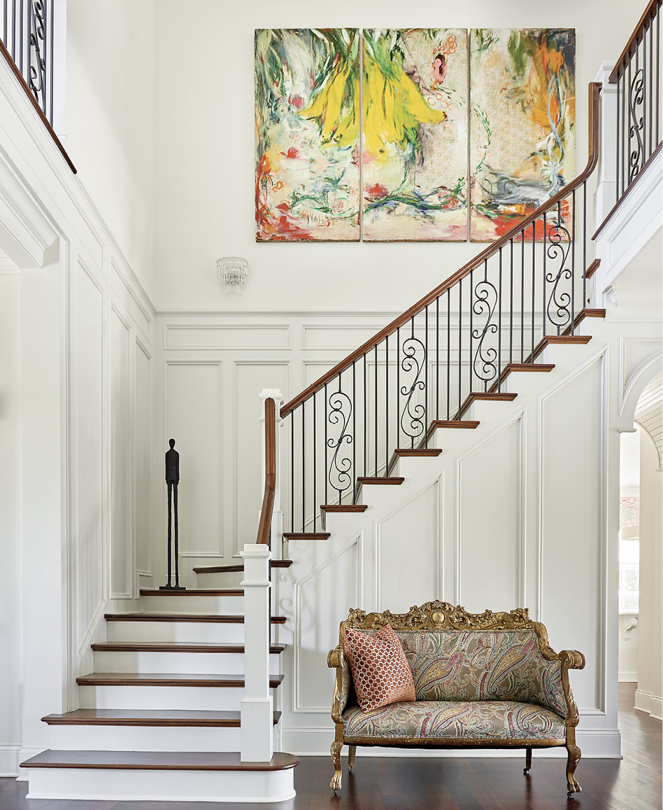 In the main stair hall, an abstract triptych by Jeannie Weissglass complements the classic English plaid from Osborne & Little on the antique French settee. The painting, says Mitchell, inspired the design throughout the home.