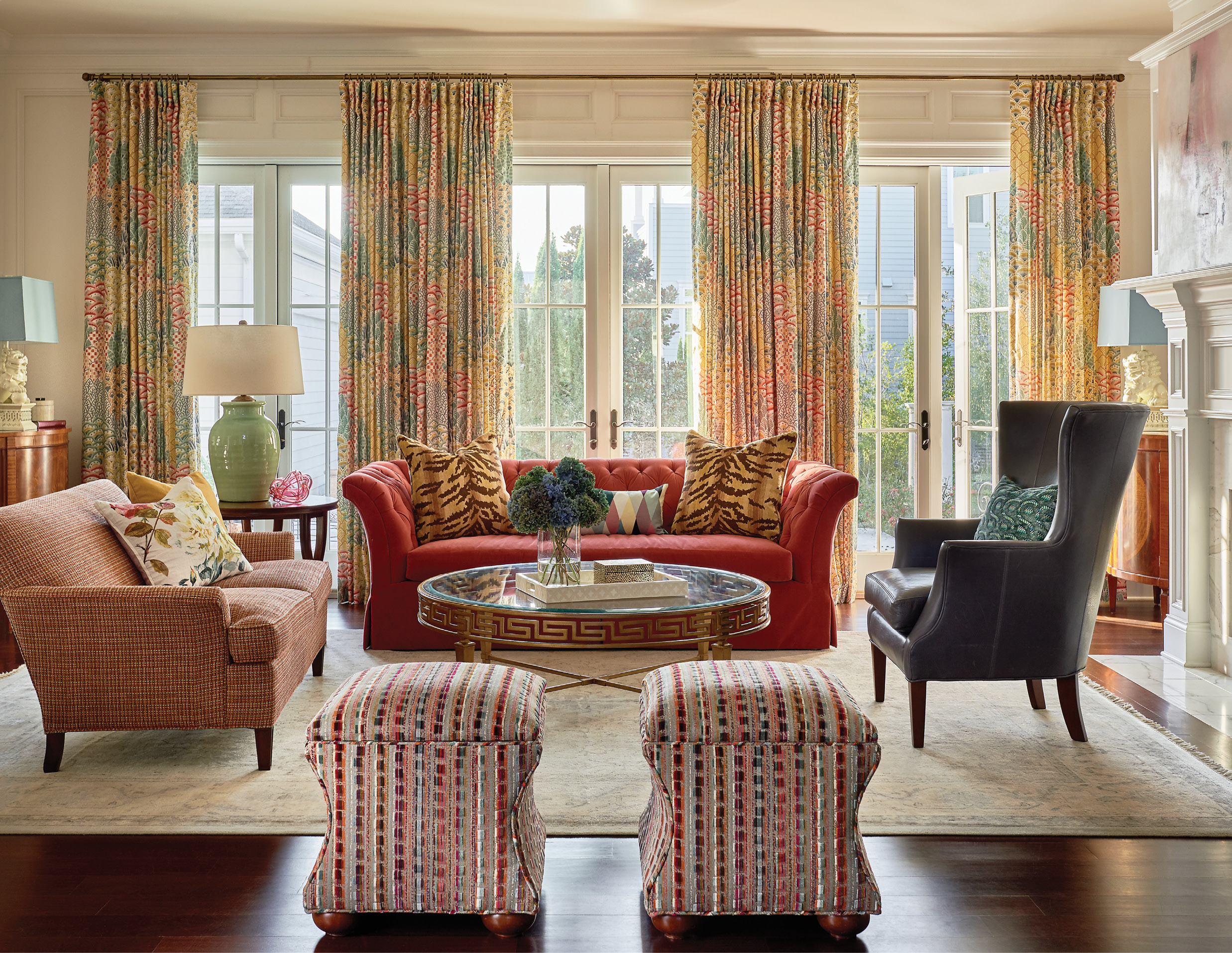 """A tufted-velvet sofa and smaller settee in a soft, sophisticated tweed offer French flair in the family room, while still providing comfort for everyday family living. The bold colors are unified by bright drapes in the Clarence House """"Shere Khan"""" fabric."""