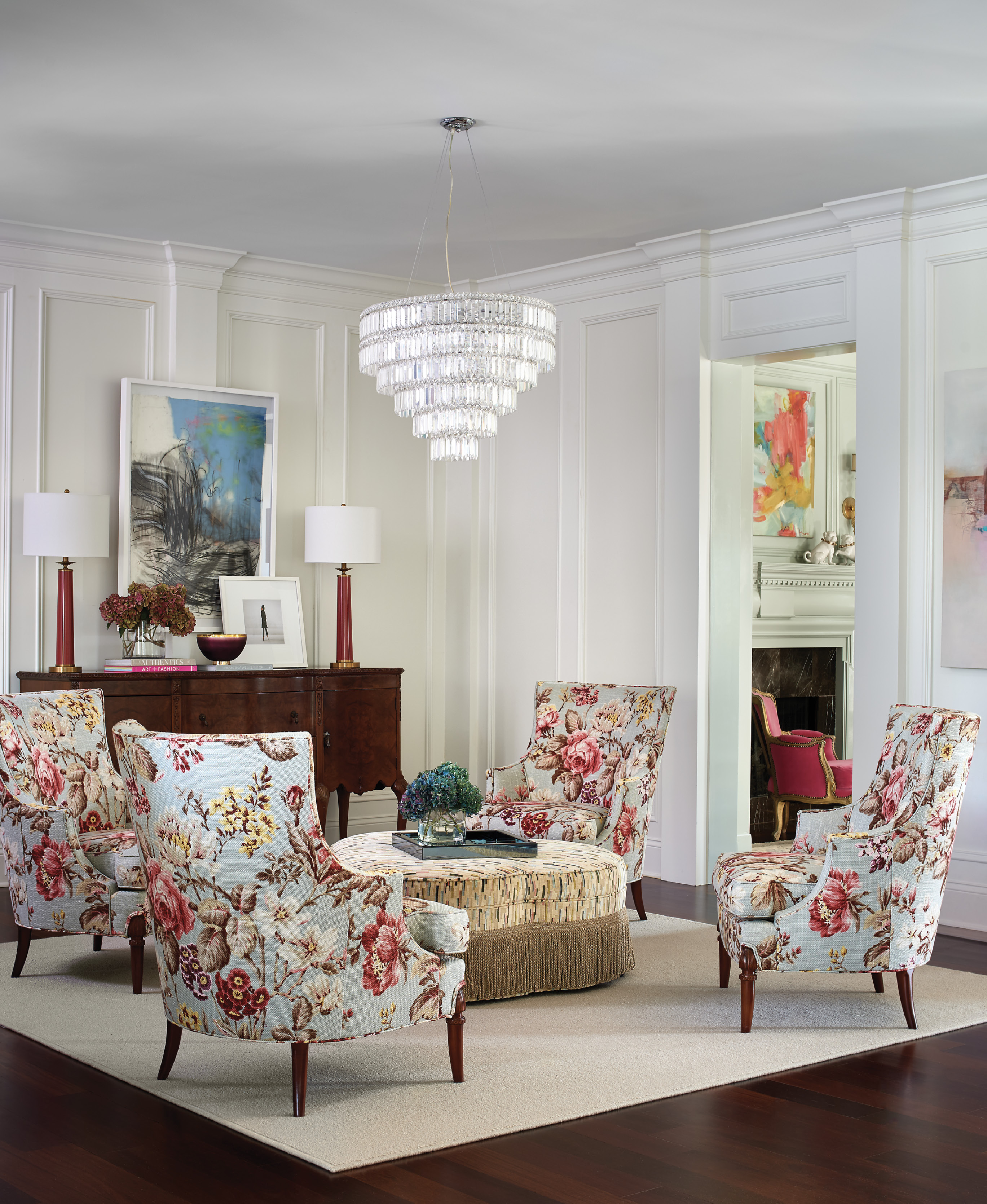 The feminine vibe from the neighboring library continues in the sitting room. A creamy area rug from Masland anchors the conversation space, with four Hickory Chair wingbacks and an ottomon covered in a Pearson fabric.