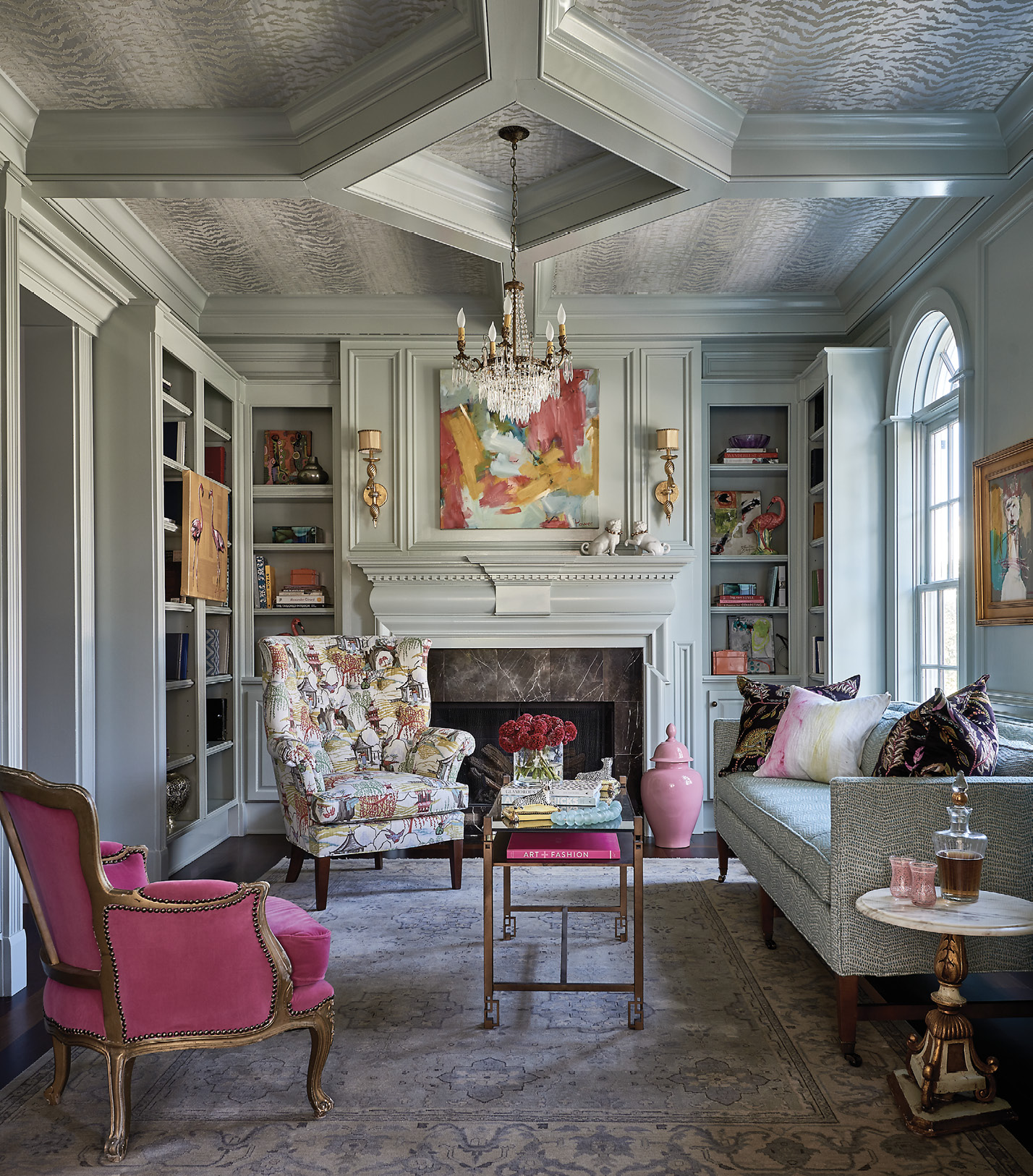 """In the library, which was previously paneled in walnut, a pale mint paint (Farrow & Ball """"Cromarty No. 285""""), Thibaut """"Tiger Flock"""" wallpaper, pops of pink, and a crystal chandelier achieved the glamorous, New Orleans-inspired aesthetic the homeowner desired."""