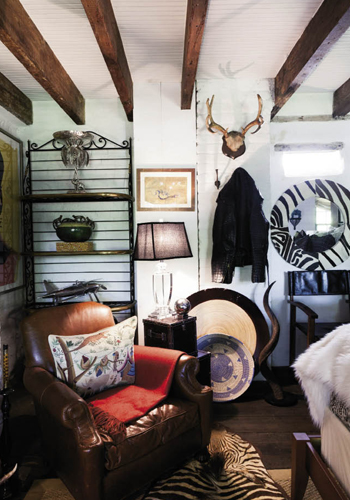 "The ""Safari Room"" features earth-toned fabrics, rugged furnishings, and African art, as well as game trophies, a zebra-skin rug, and an alligator-skin motorcycle jacket hung on the wall."