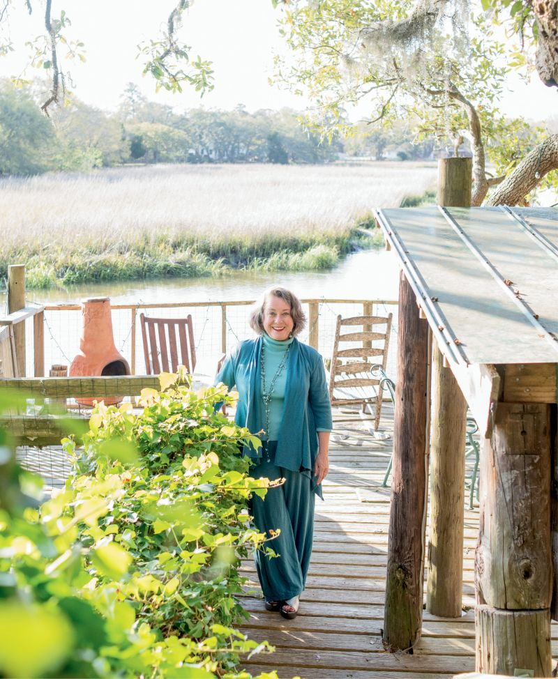 """""""I love to be outdoors,"""" says artist Mary Edna Fraser, pictured here on the dock of the James Island tidal creek property where she lives and works."""